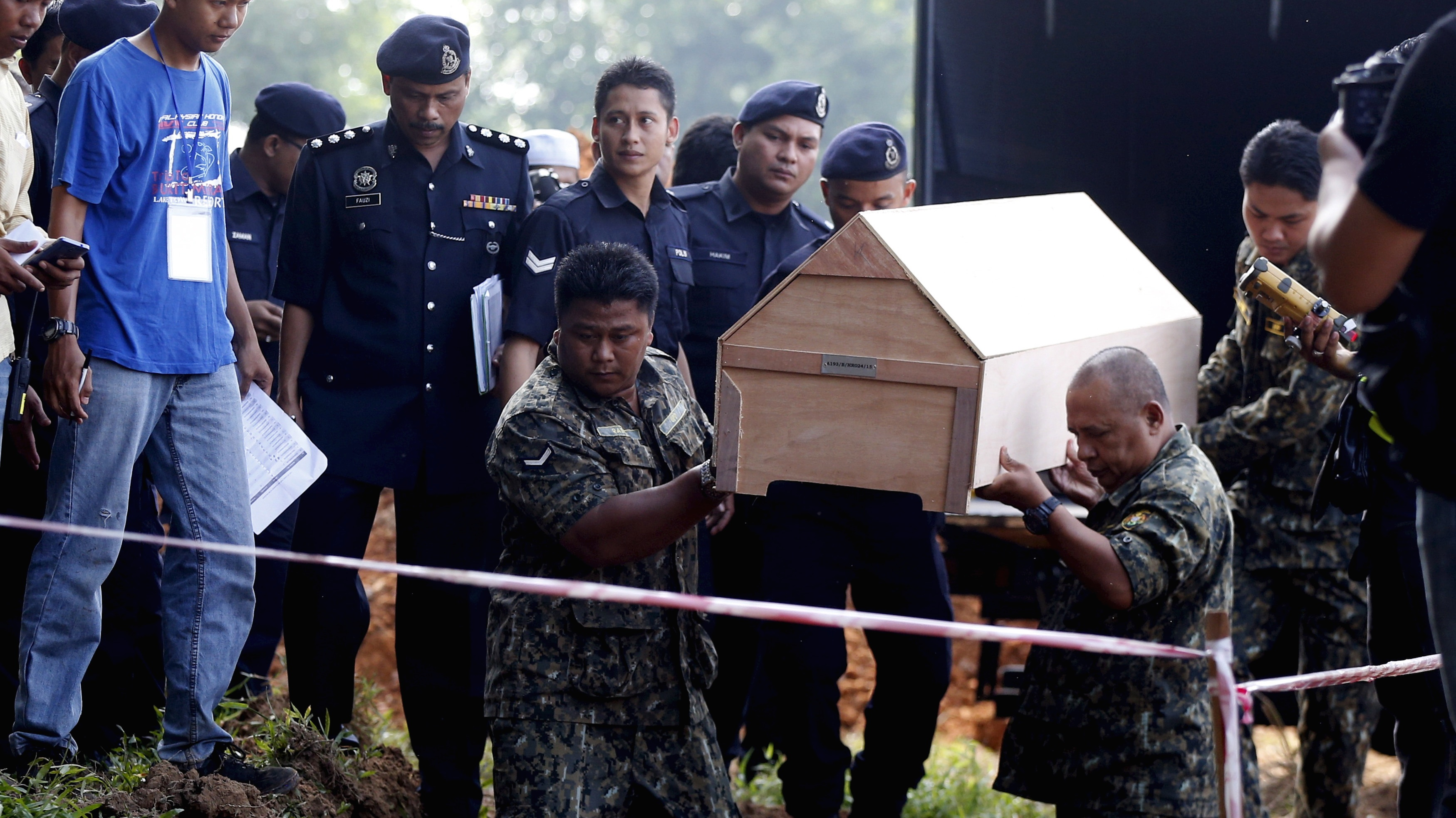Malaysian police carry a coffin with unidentified remains of Rohingya people found at a traffickers camp on the border with Thailand.