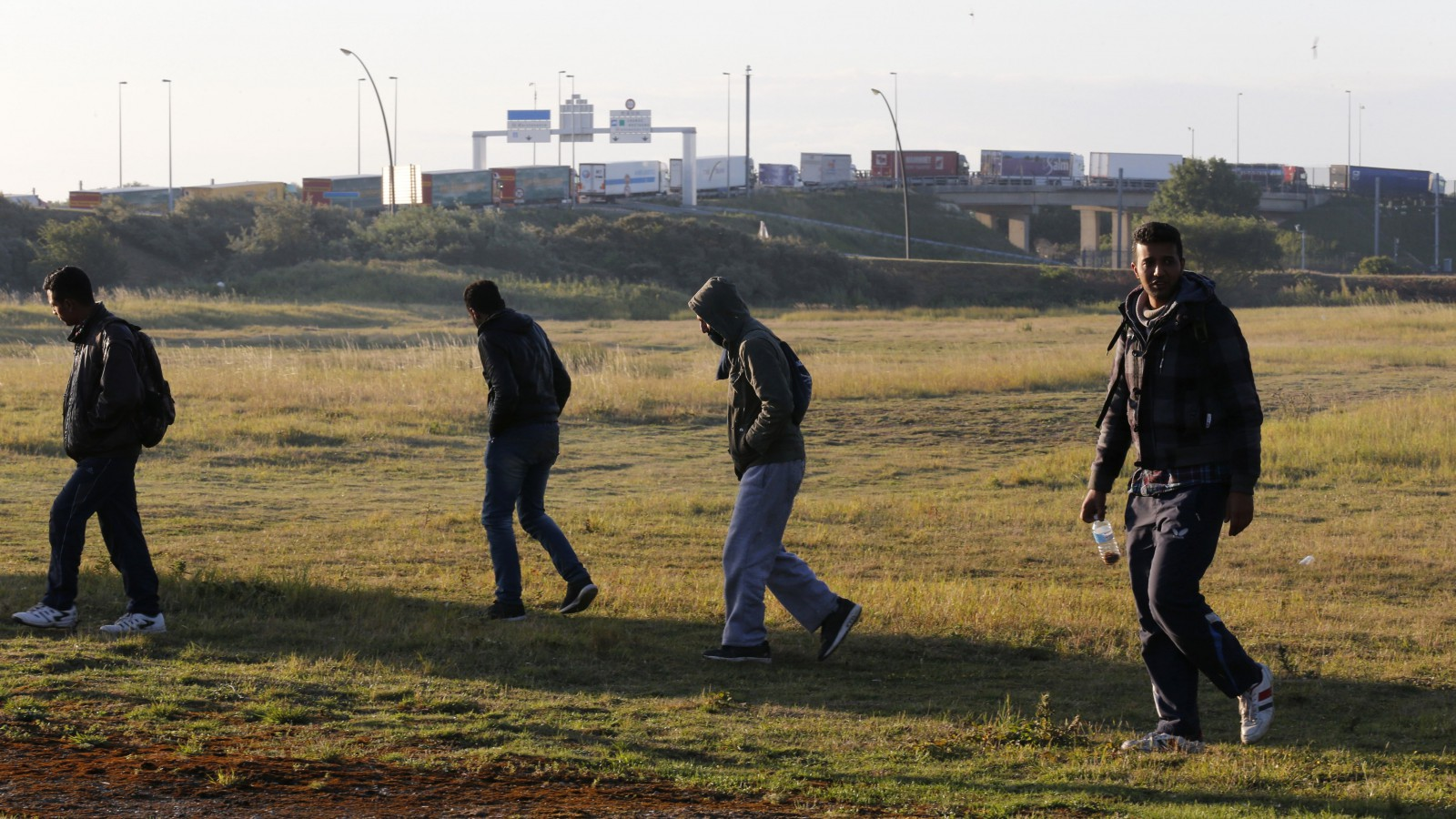 Migrants walk near the road after they left their hiding spot at the Eurotunnel site early in the morning as lorries queue to embark on shuttles at the Eurotunnel terminal in Calais, northern France, July 29, 2015. A migrant died trying to cross to Britain from France early on Wednesday, French police said, adding to a number of recent deaths in the Channel Tunnel as British ministers and security chiefs were to meet over the crisis in Calais. There were about 1,500 attempts by migrants to access the tunnel on Tuesday night, a Eurotunnel spokesman said, after 2,000 attempts the previous night.    REUTERS/Pascal Rossignol - RTX1M8AJ