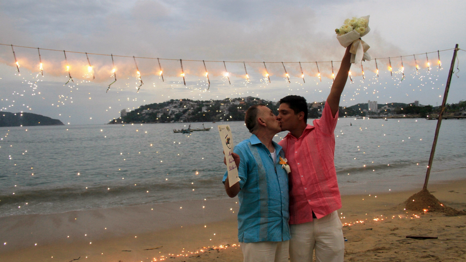 A couple kisses after taking part in a group wedding in Acapulco, Mexico, July 10, 2015. Twenty gay and lesbian couples tied the knot in a group wedding on Friday, in a ceremony organised by the local government, one month after Mexico's Supreme Court ruled that laws restricting marriage to a man and a woman were unconstitutional, local media reported. REUTERS/Claudio Vargas