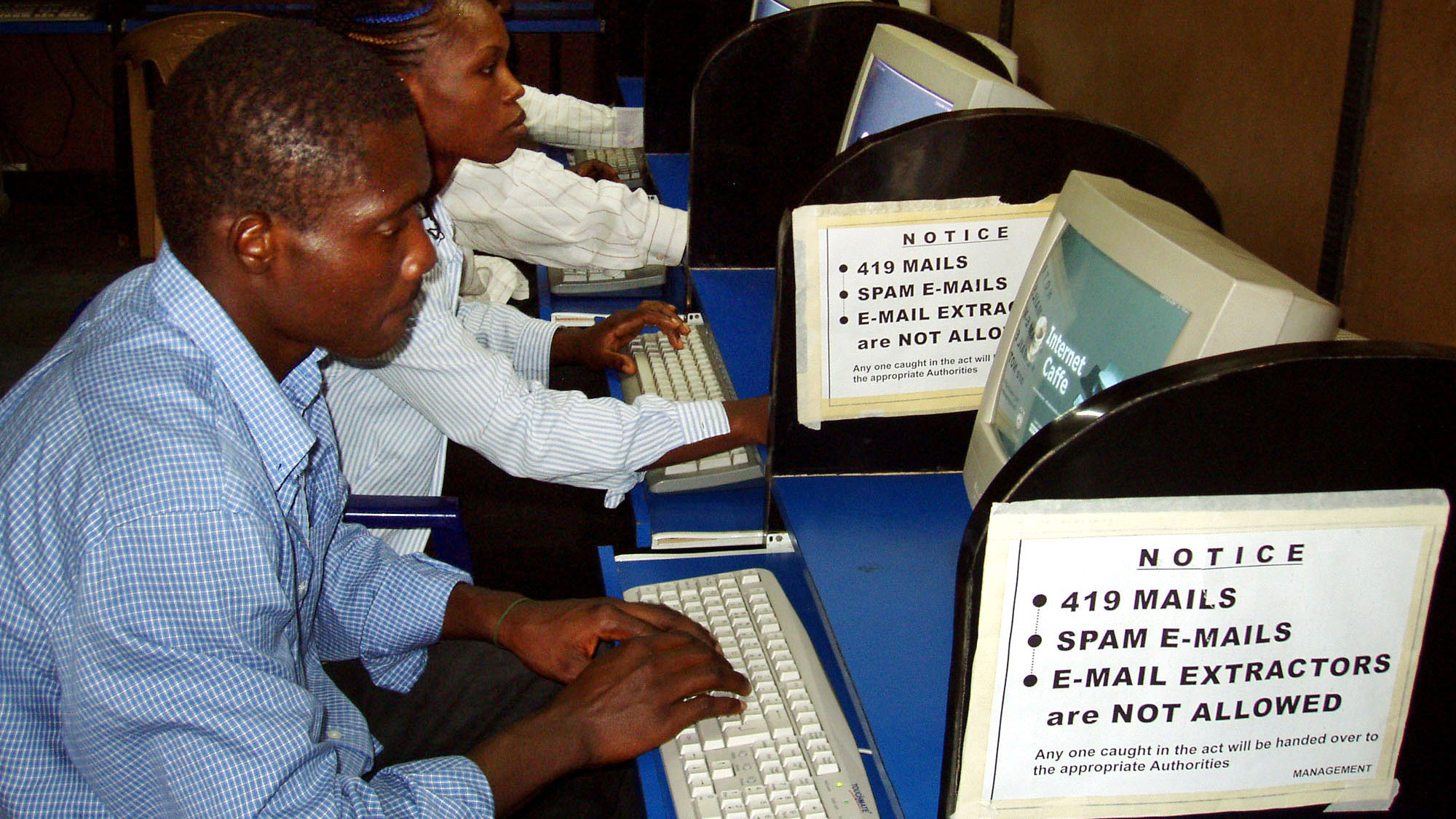 Nigerians surrounded by warning signs about sending fraudulent e-mail wait to use the Internet in an Internet cafe in Lagos, Nigeria Sunday, July 17, 2005. Nigerian police say they've scored results in a crackdown launched by President Olusegun Obasanjo's government in the past three years on such crime - which had grown to the point that it is associated with Nigeria all over the world - but new scammers are appearing and evolving new ruses to both trap victims and evade detection.