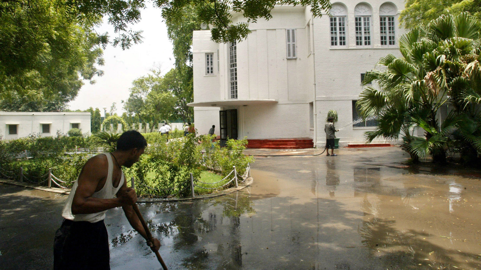 Maintenance staff clean the government-owned property at 33 Shamnath Marg in New Delhi, India, on Saturday, June 26, 2004. The bungalow, with its enormous yard, cavernous living room, quarters for seven servants and a guard house, but believed to be jinxed, will be occupied after two years sitting empty by newly-appointed New Delhi Lt. Gov. B.L. Joshi.(AP Photo/Manish Swarup)