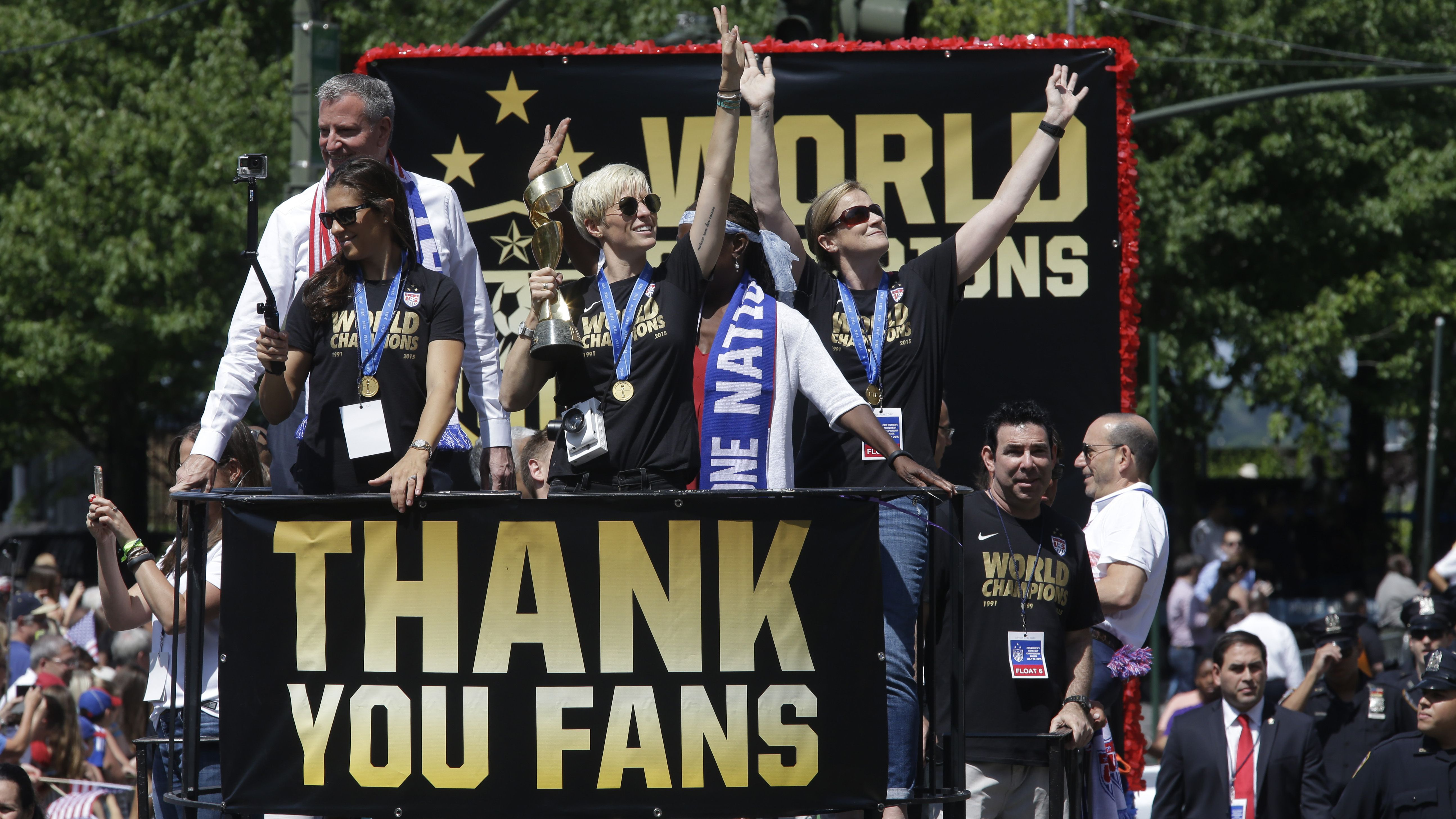 U.S. women's soccer team midfielder Megan Rapinoe, center, holds up the World Cup trophy while midfielder Carli Lloyd, left, New York City Mayor Bill de Blasio, left background, and head coach Jill Ellis, right, wave to the crowd as their float makes it way up Broadway's Canyon of Heroes during the ticker tape parade to celebrate the U.S. women's soccer team World Cup victory, Friday, July 10, 2015, in New York. (AP Photo/Mary Altaffer)