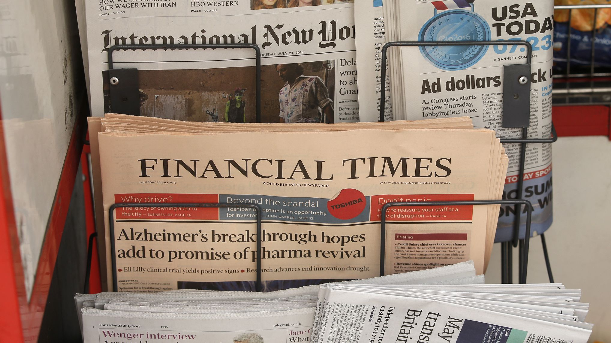"""Copies of the Financial Times newspaper sit in a rack at a newsstand in London, Britain July 23, 2015. British publisher Pearson has decided to sell the Financial Times to a """"global, digital news company"""" after owning the business newspaper for nearly 60 years, a person familiar with the deal said on Thursday. Pearson, which has become the world's leading education provider, later confirmed that it was in advanced discussions regarding a potential disposal of FT group, which includes the pink-paged paper, its website and its share in the Economist, but declined to provide further details. REUTERS/Peter Nicholls"""