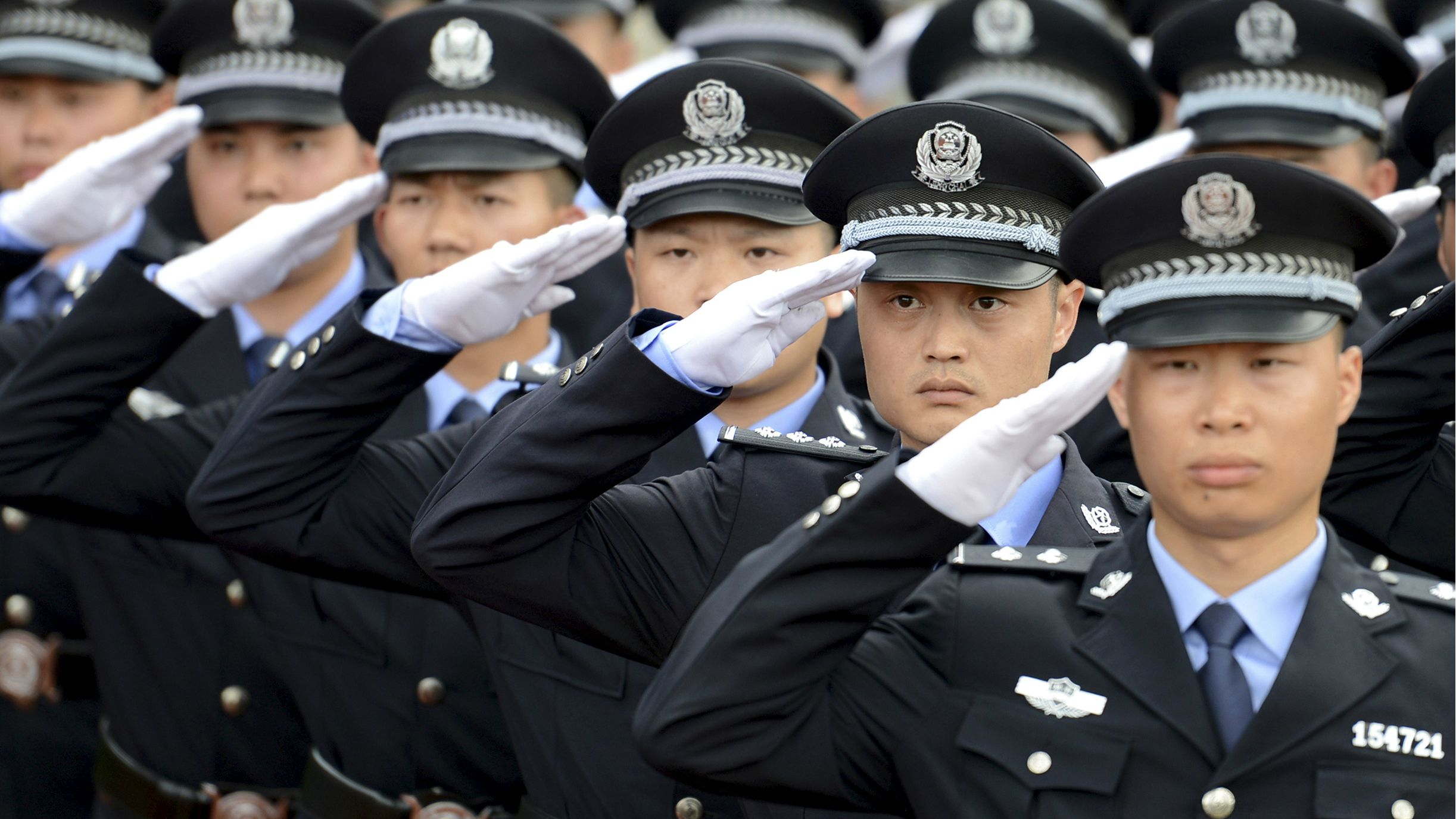 Policemen salute as they march in formation during the opening ceremony of a police sports assembly in Chenzhou, Hunan province, China, June 10, 2015. Picture taken June 10, 2015. REUTERS/Stringer