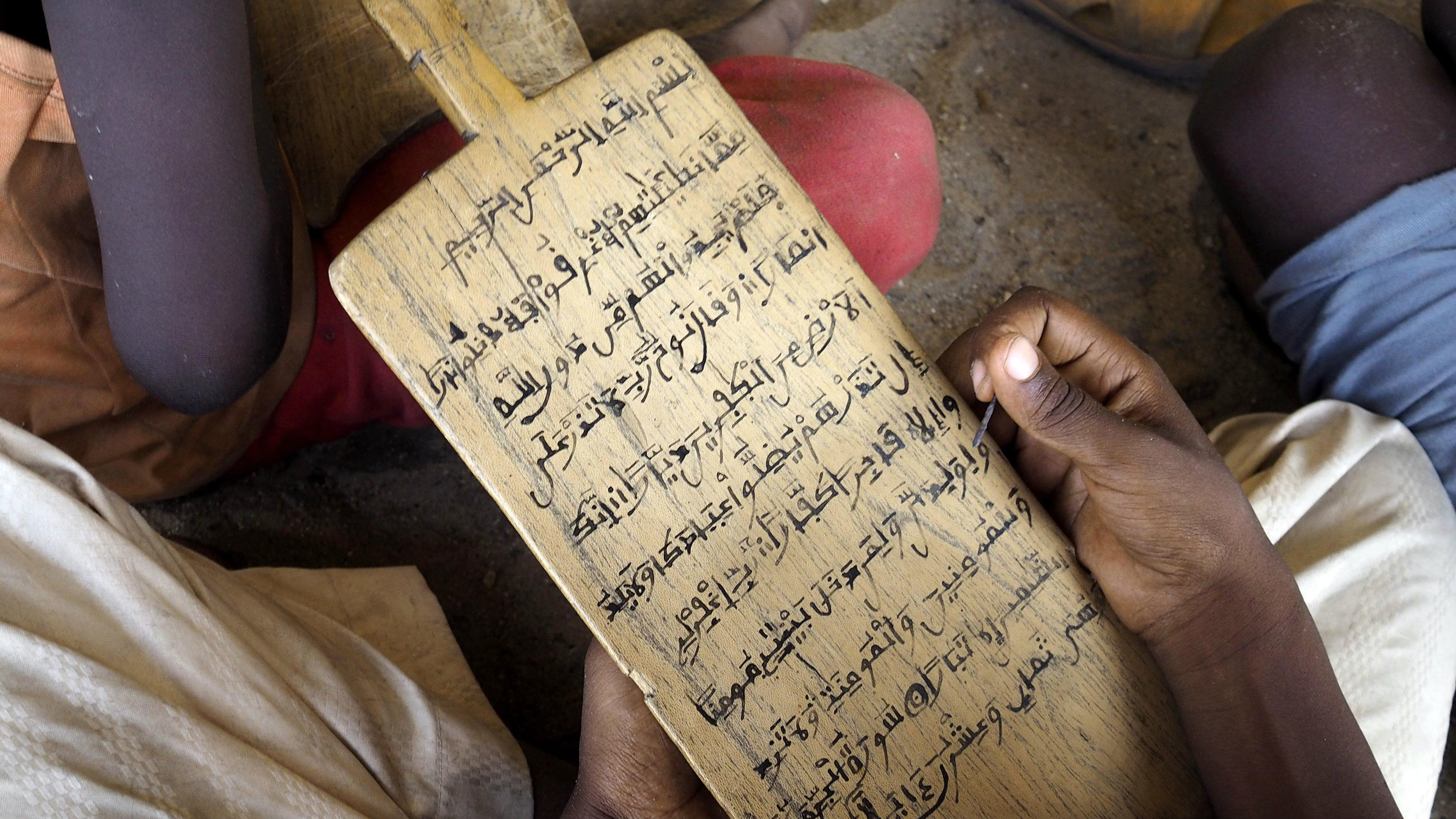 A boy holds a slate of wood with Quranic verses written on them at an Almajiri Islamic school in Maiduguri, Nigeria, May 24, 2014.
