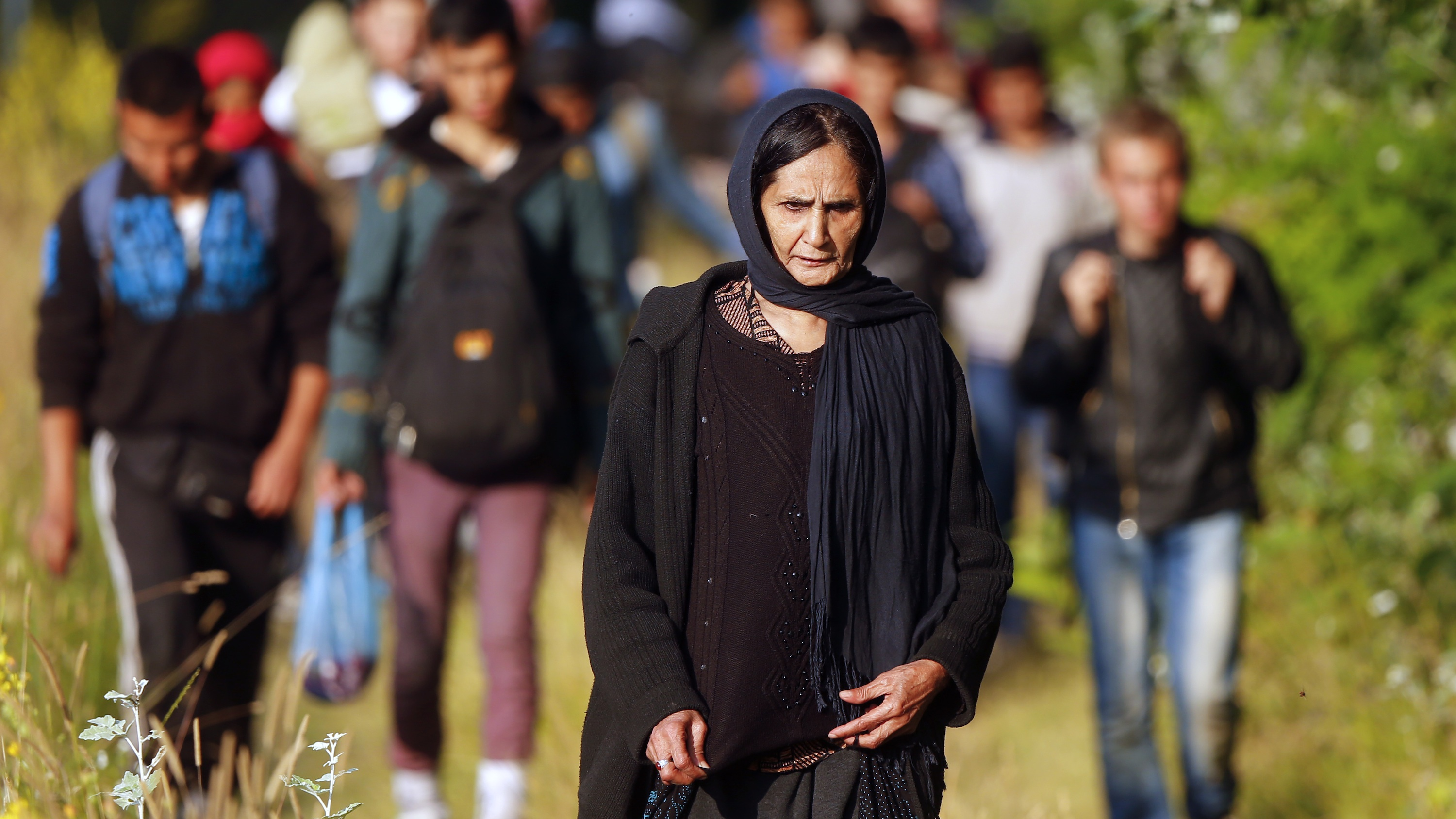 Refugees from Afghanistan walk after crossing the border from Serbia into Hungary.