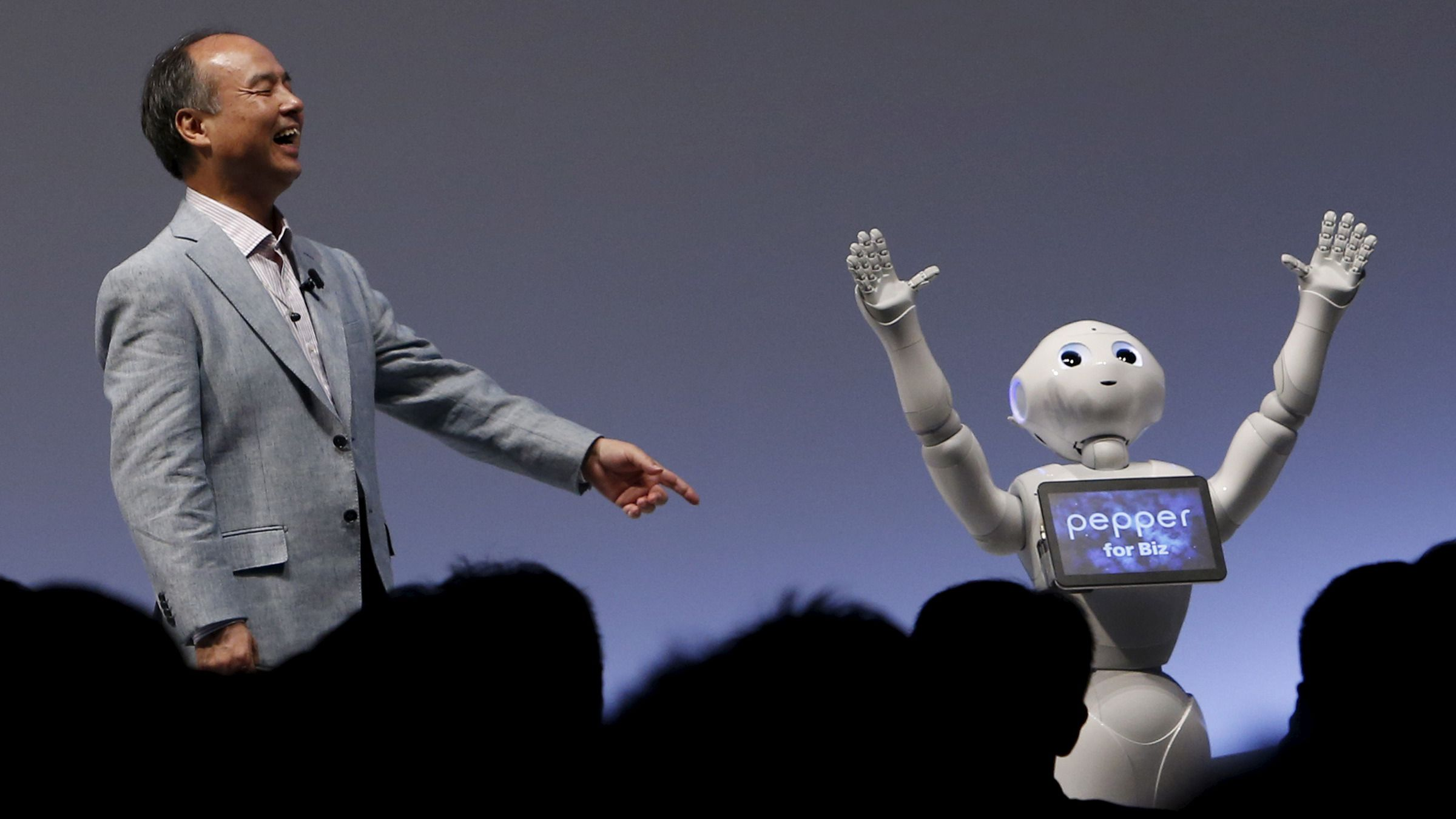 """SoftBank Group Corp. Chairman and CEO Masayoshi Son reacts as SoftBank's human-like robots named """"Pepper"""" performs during the SoftBank World 2015 event in Tokyo, Japan, July 30, 2015."""