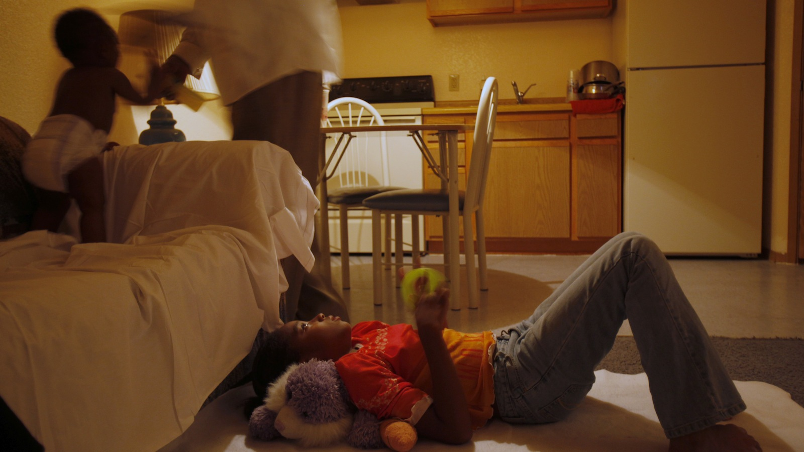 Frederick Wilson, (C), puts his eleven month old granddaughter, Keziah Bradley, to bed on the couch as his niece, Kayla Miles, 12, lays on the floor where she will sleep inside the motel room the where the family is living in Grand Prairie, Texas June 30, 2009.  This is the first night the family has had sheets to sleep on after it was brought to the attention of the Urban League, who is paying for the room, that the motel charged extra for sheets. After much discussion the Urban League was able to convince the motel owners to provide sheets for the family. The Wilson family moved to Texas after losing their jobs and their home in Minnesota. They ended up in a homeless shelter and through assistance with the National Urban League were able to find jobs, the Urban League has been paying for temporary housing in a motel as they work to get back on their feet. REUTERS/Jessica Rinaldi (UNITED STATES) - RTR25ECI