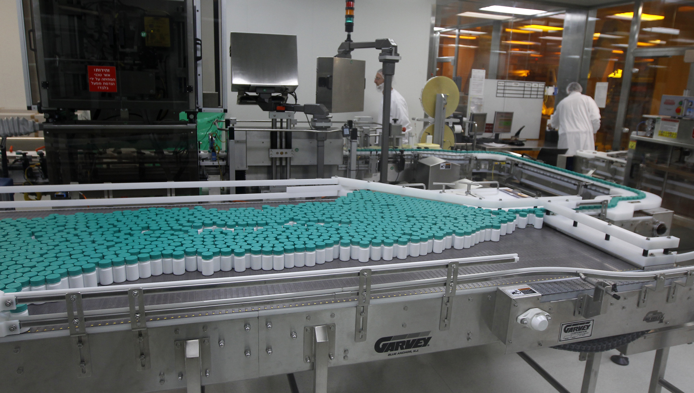 Employees of Teva Pharmaceutical Industries work near pill bottles on a conveyor belt at the company's Jerusalem oral solid dosage plant (OSD) December 21, 2011. Israel-based Teva is the world's leading generic drugmaker.   REUTERS/Ronen Zvulun  (JERUSALEM - Tags: BUSINESS DRUGS SOCIETY) - RTR2VIEP