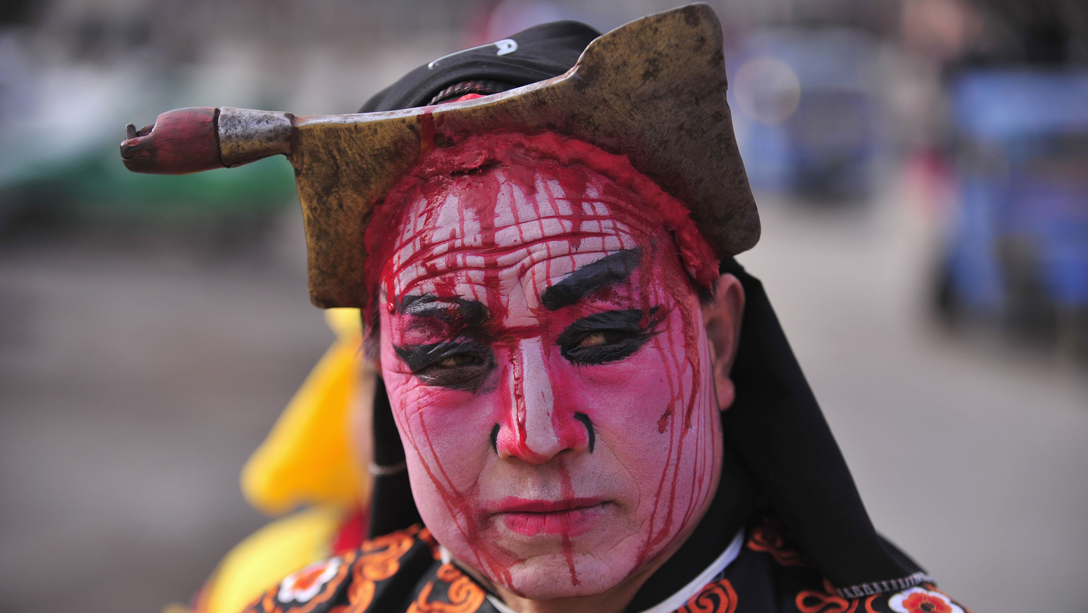 """A folk performer with his face painted to appear as knife cuts, and wearing a knife prop on his head, takes part in a """"Blood Shehuo"""" parade to celebrate the Lantern Festival on the last day of the Chinese Lunar New Year celebrations at Chisha village in Baoji, Shaanxi province February 6, 2012. """"Shehuo"""" is common name of Chinese traditional activities consisting of folk performances in Northern China. The """"Blood Shehuo"""" performers wear facial makeup to appear as being pierced by objects including axes, scissors and knives, featuring scenes of horror in traditional stories like Water Margin. This activity is held only in Baoji county and performed only during leap years. REUTERS/Rooney Chen"""