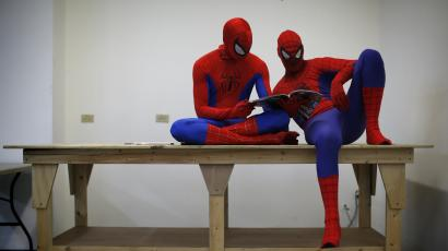 "Peter Norbot and Kris Hamilton (L), dressed up as fictional comic book superhero Spider-Man, look through a magazine as they wait for their turn to audition to be a part of a promotional campaign for the upcoming release of the new movie ""The Amazing Spider-Man 2"" in Chicago March 19, 2014."