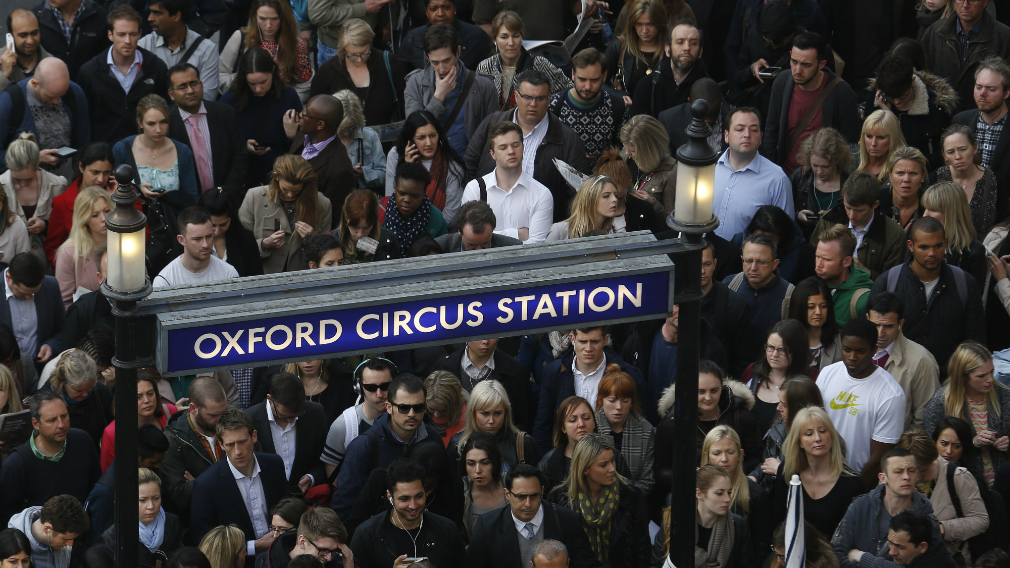 Commuters and shoppers queue for access to Oxford Circus underground station.