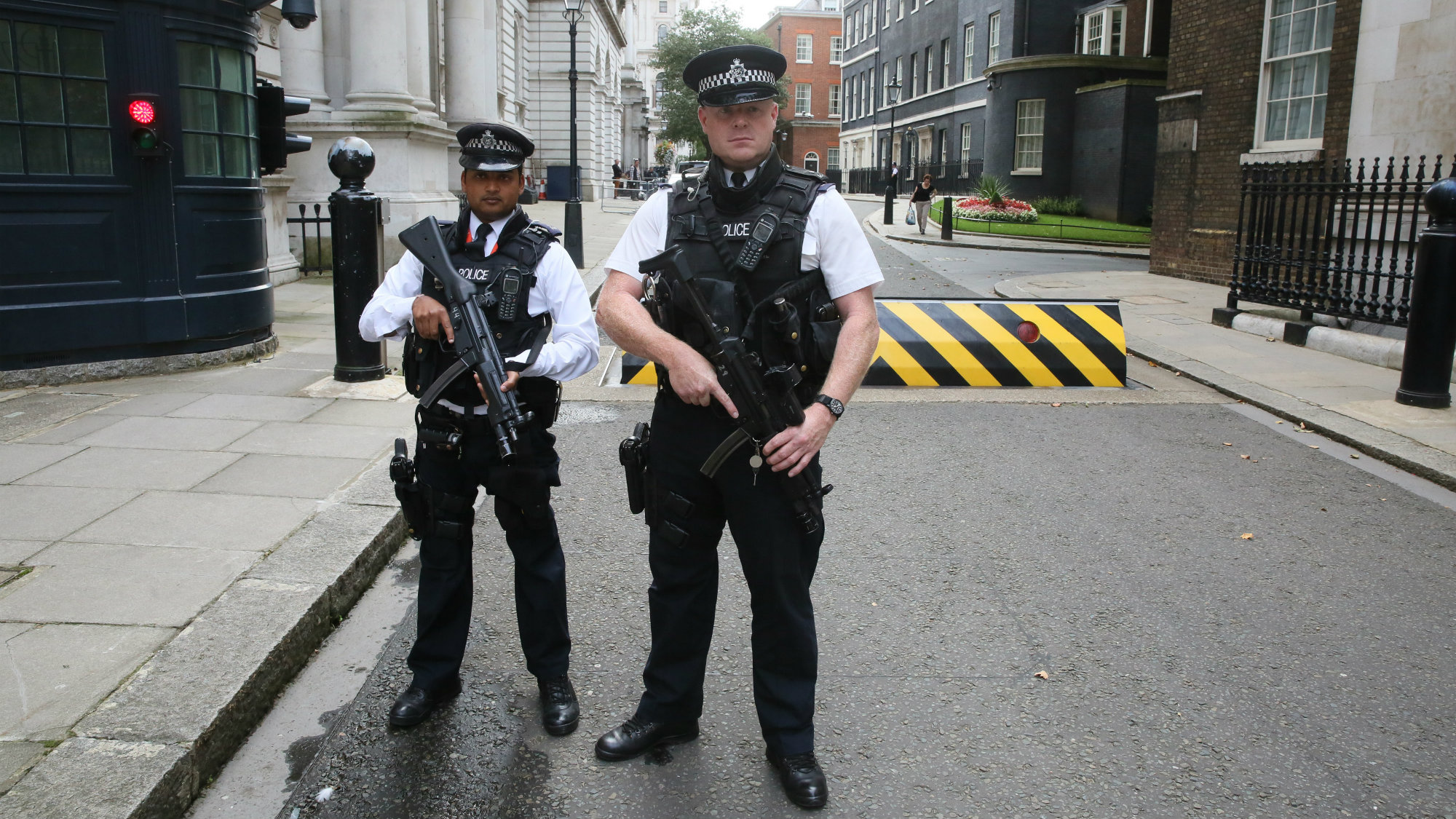 Armed police officers pose for the media in Downing Street, central London.