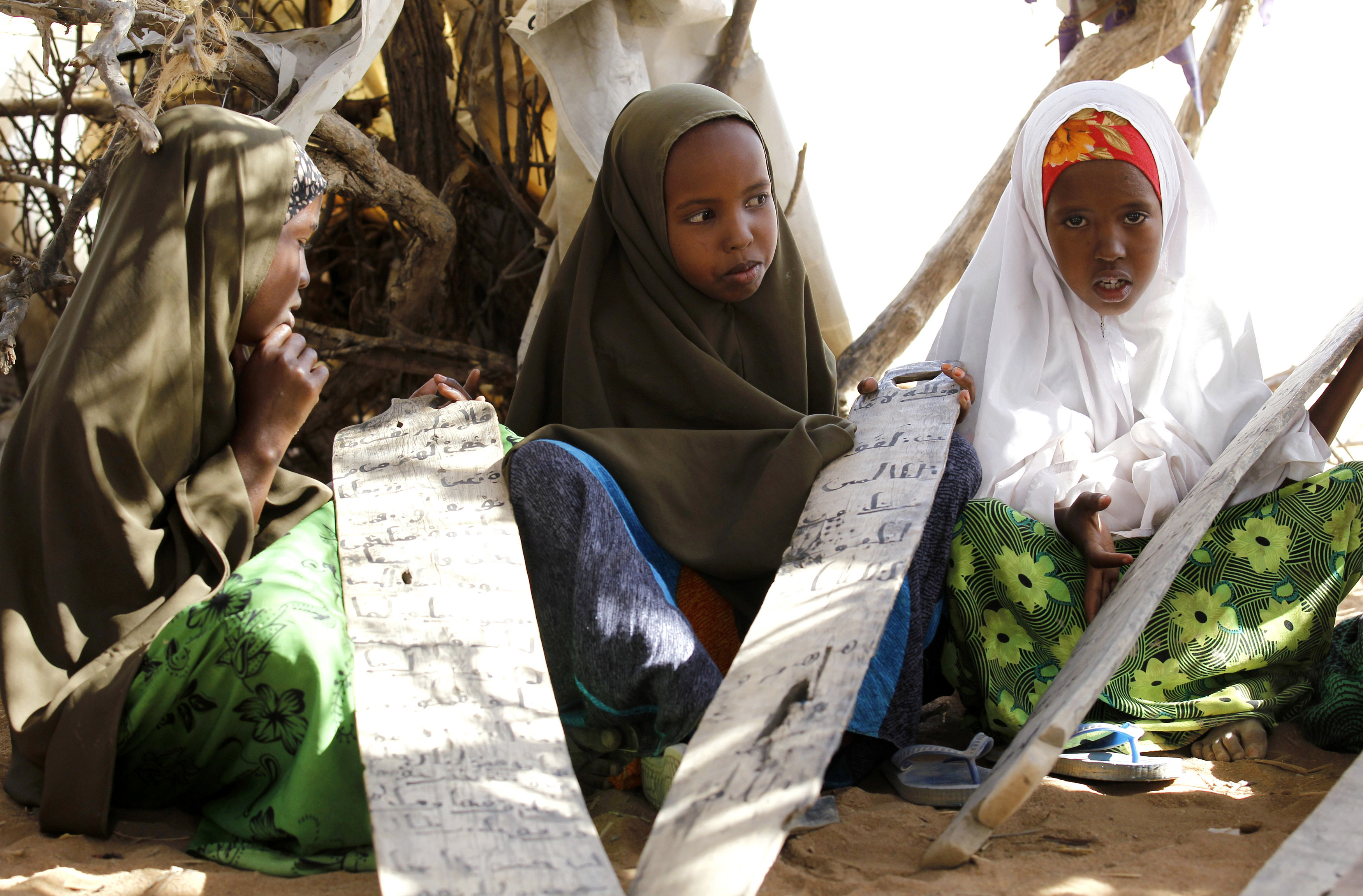 Refugee pupils hold pieces of wood with Quranic verses written on them at a makeshift madrasa, or Islamic school, under a tree at the IFO2 east camp within the Dadaab refugee complex, near the Kenya-Somalia border, October 29, 2014. REUTERS/Thomas Mukoya (KENYA - Tags: EDUCATION SOCIETY RELIGION)