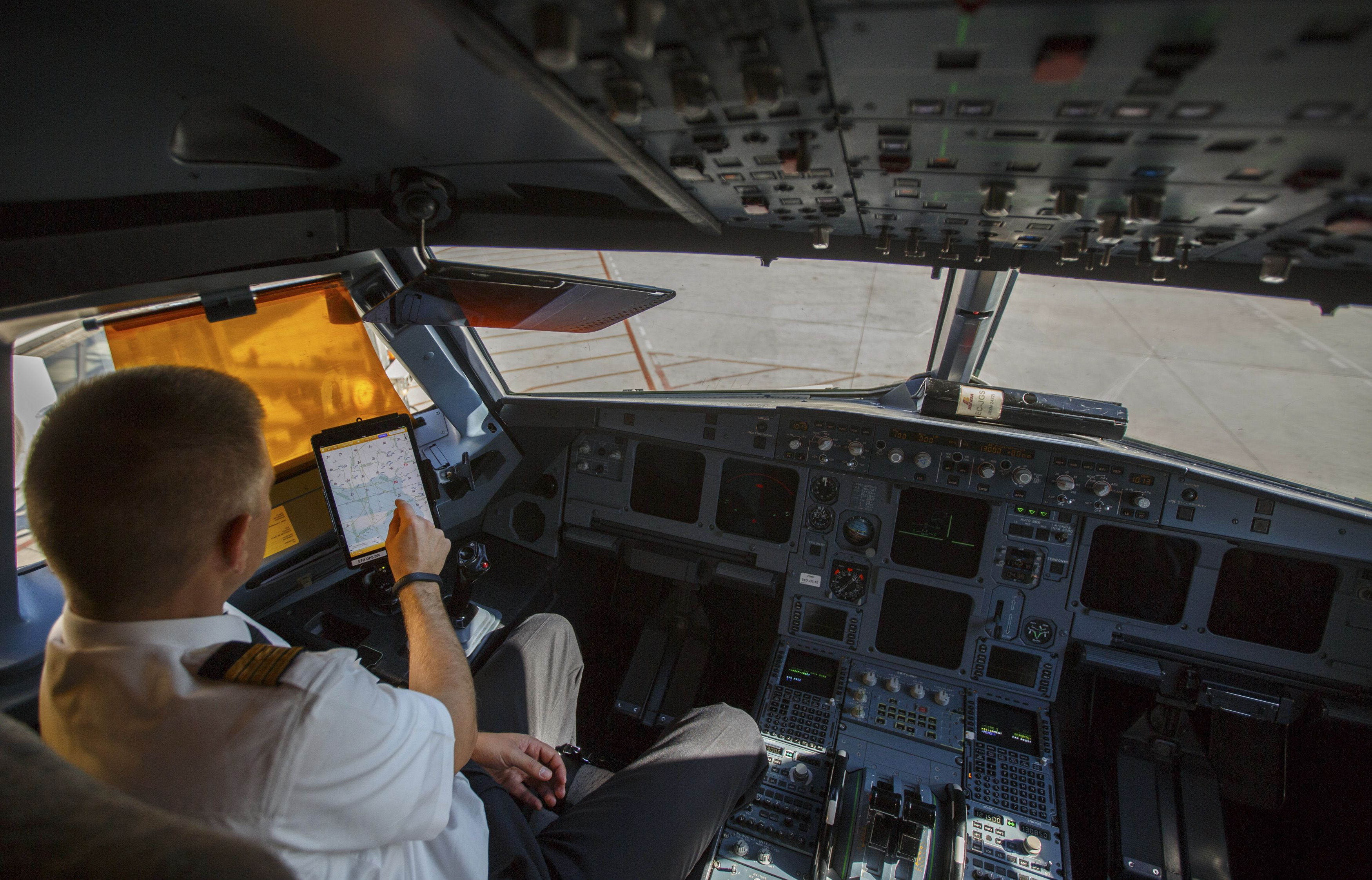 An Iberia Airlines pilot touches the screen of an iPad during a demonstration inside a cockpit of a passenger plane at Terminal 4 of Madrid's Adolfo Suarez Barajas airport