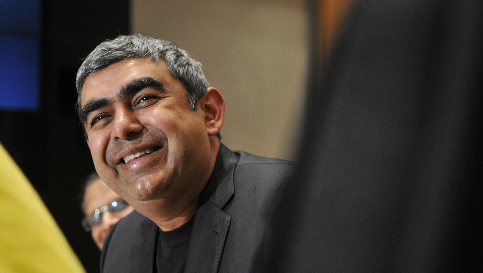 Infosys Chief Executive Officer Vishal Sikka smiles during the announcement of the company's quarterly financial results at its headquarters in the southern Indian city of Bengaluru January 9, 2015. Shares in software services exporter Infosys Ltd rose almost 7 percent on Friday after it surprised investors by sticking to its full-year sales target, thanks to healthy demand that helped offset the impact of a stronger dollar. Infosys, which posted a 13 percent rise in third-quarter profit, confirmed it expects sales growth of 7 to 9 percent for the year ending in March 2015, in constant currency terms and based on exchange rates for the September quarter.