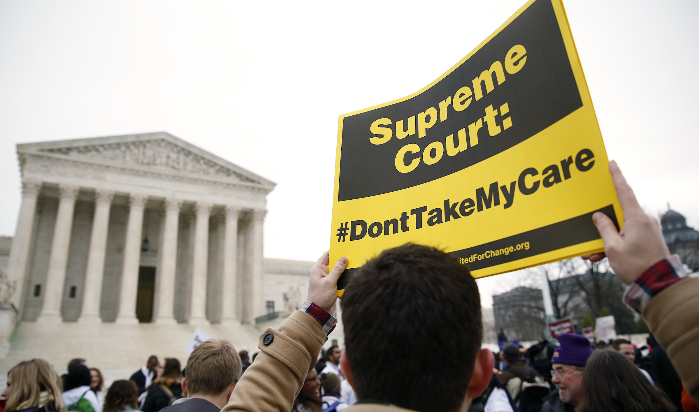 A demonstrator in favor of the Affordable Care Act walks with a sign in front of the Supreme Court in Washington March 4, 2015. The U.S. Supreme Court will weigh a second major case, King v. Burwell, targeting President Barack Obama's healthcare law on Wednesday when it considers a conservative challenge to tax subsidies critical to the measure's implementation.       REUTERS/Gary Cameron     (UNITED STATES - Tags: POLITICS HEALTH) - RTR4S1YH