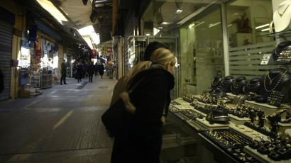 Shoppers look at jewelry in a window in the Plaka old district in Athens.