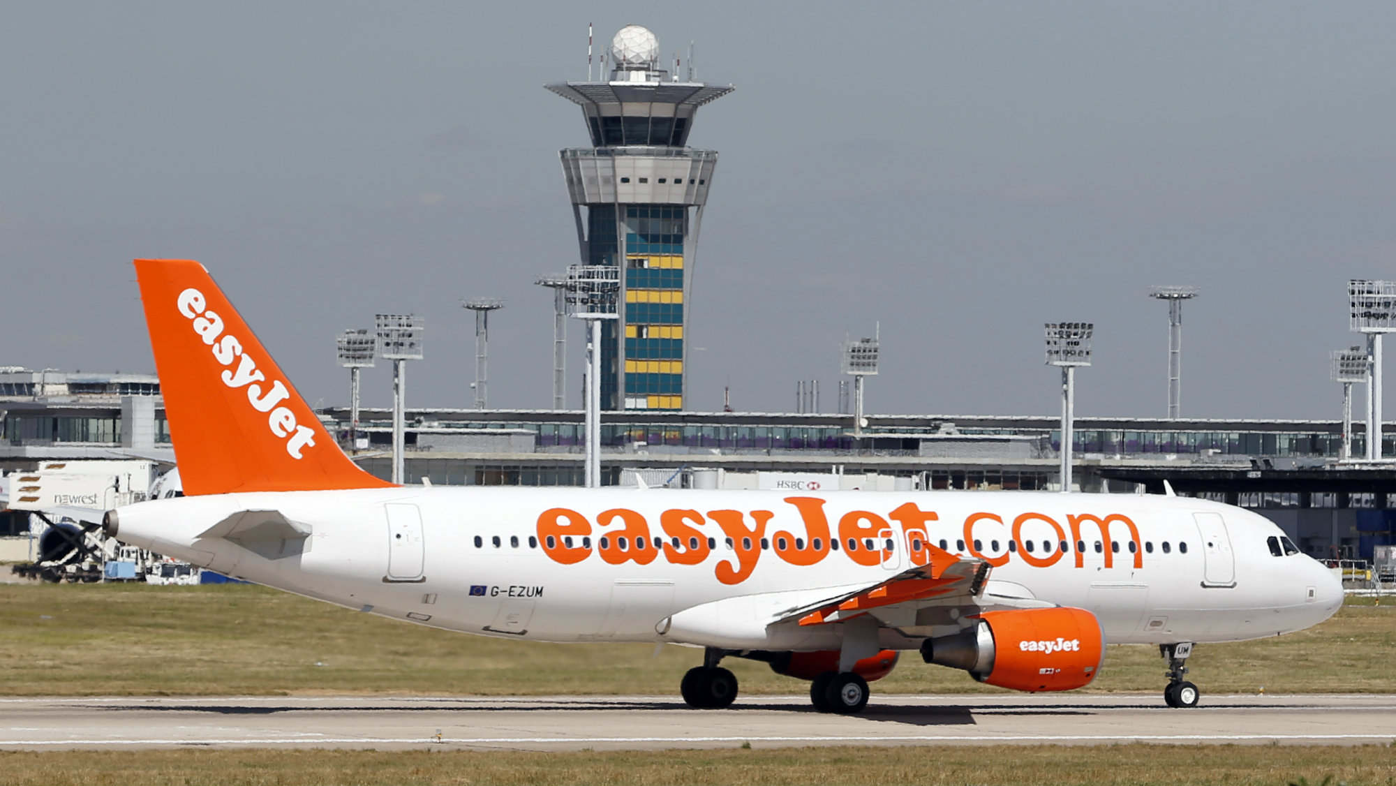 An Airbus A320 EasyJet passenger plane passes by the air traffic control tower as it prepares for take off at Orly Airport, near Paris.
