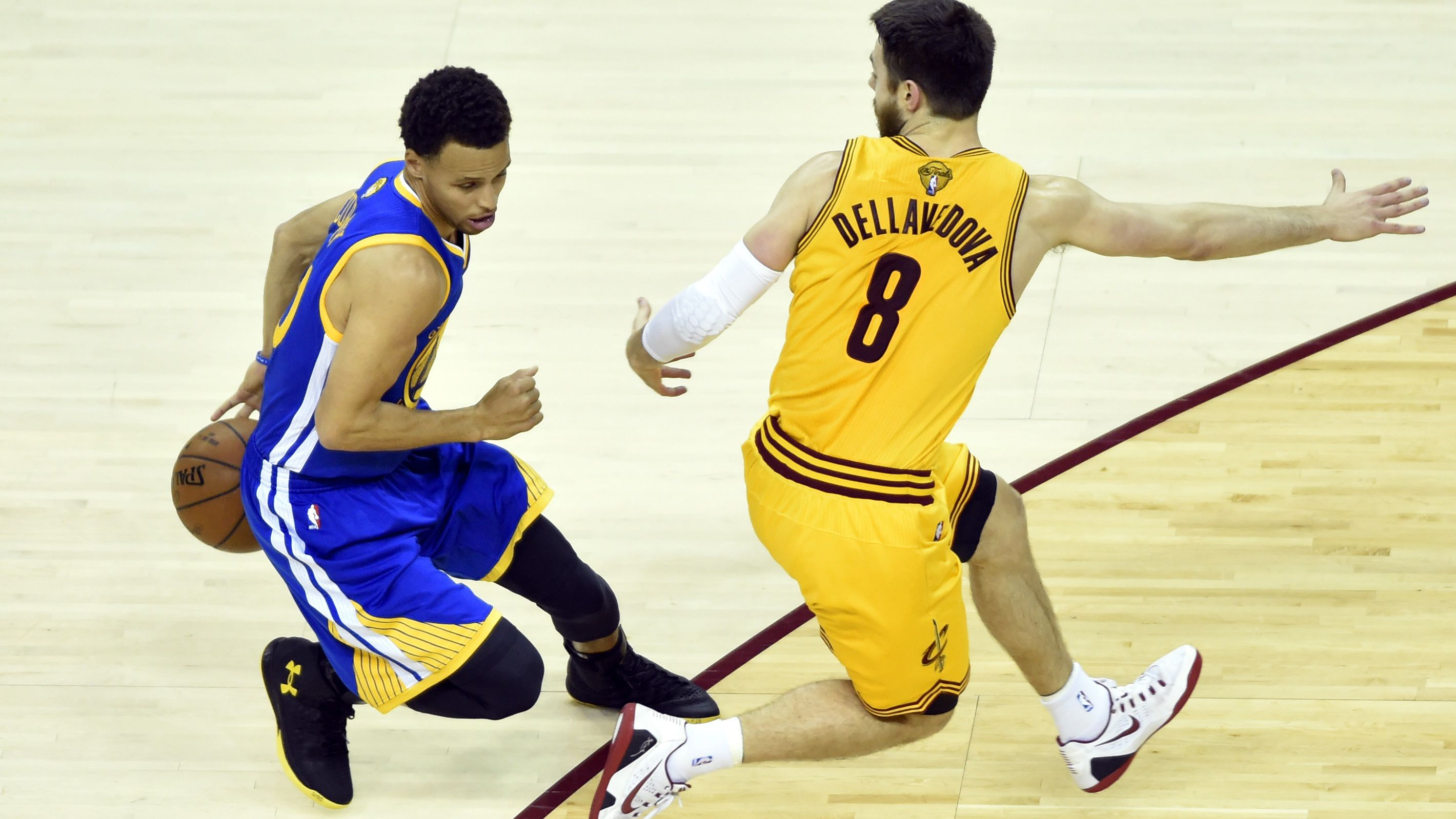 Jun 11, 2015; Cleveland, OH, USA; Golden State Warriors guard Stephen Curry (30) controls the ball against Cleveland Cavaliers guard Matthew Dellavedova (8) during the first quarter of game four of the NBA Finals at Quicken Loans Arena.