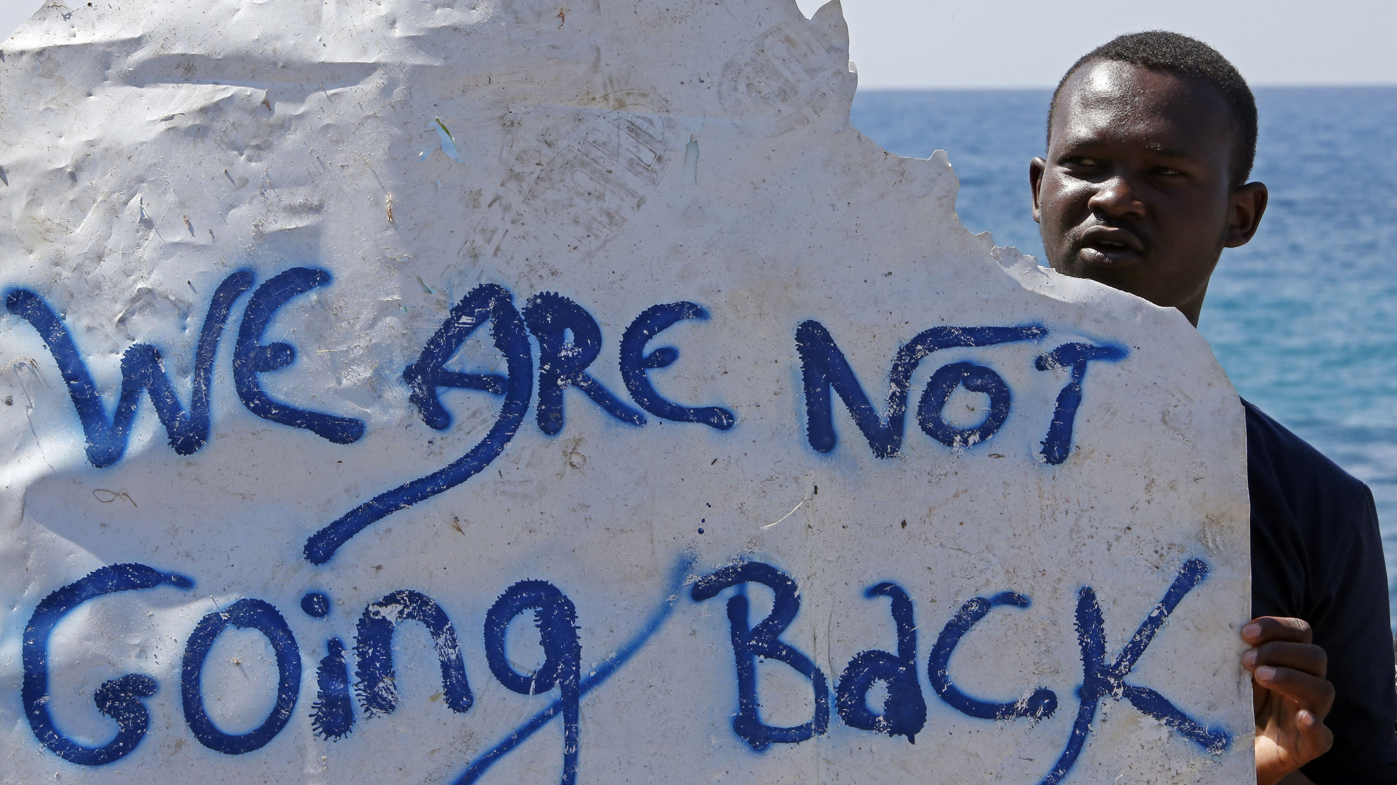 A migrant holds a banner at the Saint Ludovic border crossing on the Mediterranean Sea between Vintimille, Italy and Menton in France