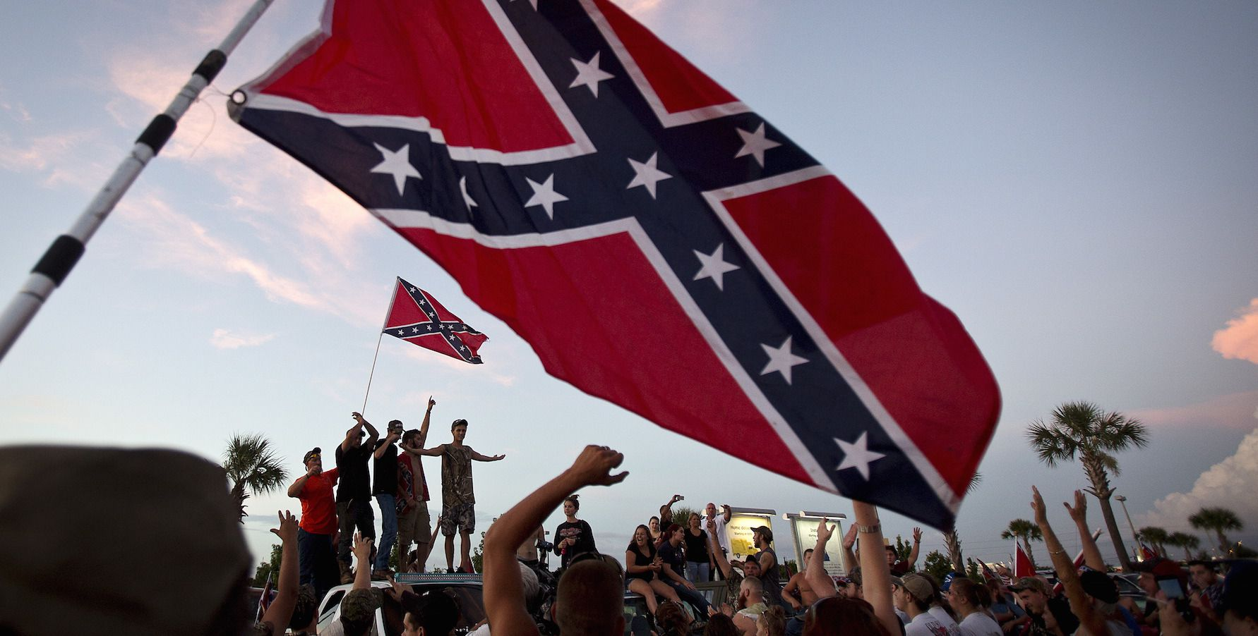 "Participants in the ""Ride for Pride"" event stand on the back of their pickup truck as they speak to an assembled crowd during the impromptu event to show their support the Confederate flag in Brandon, Hillsborough County, June 26, 2015. Several hundred people took part in the event. REUTERS/Carlo Allegri - RTX1I0AI"