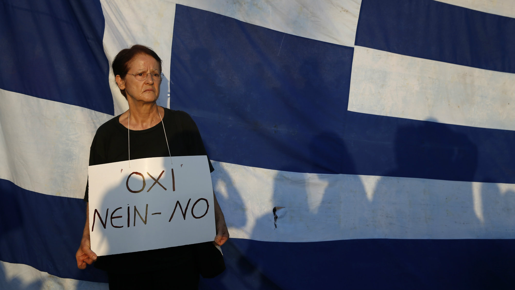 A woman holds a banner as she stands in front of a Greek flag during an anti-austerity rally in Athens, Greece, June 29, 2015.