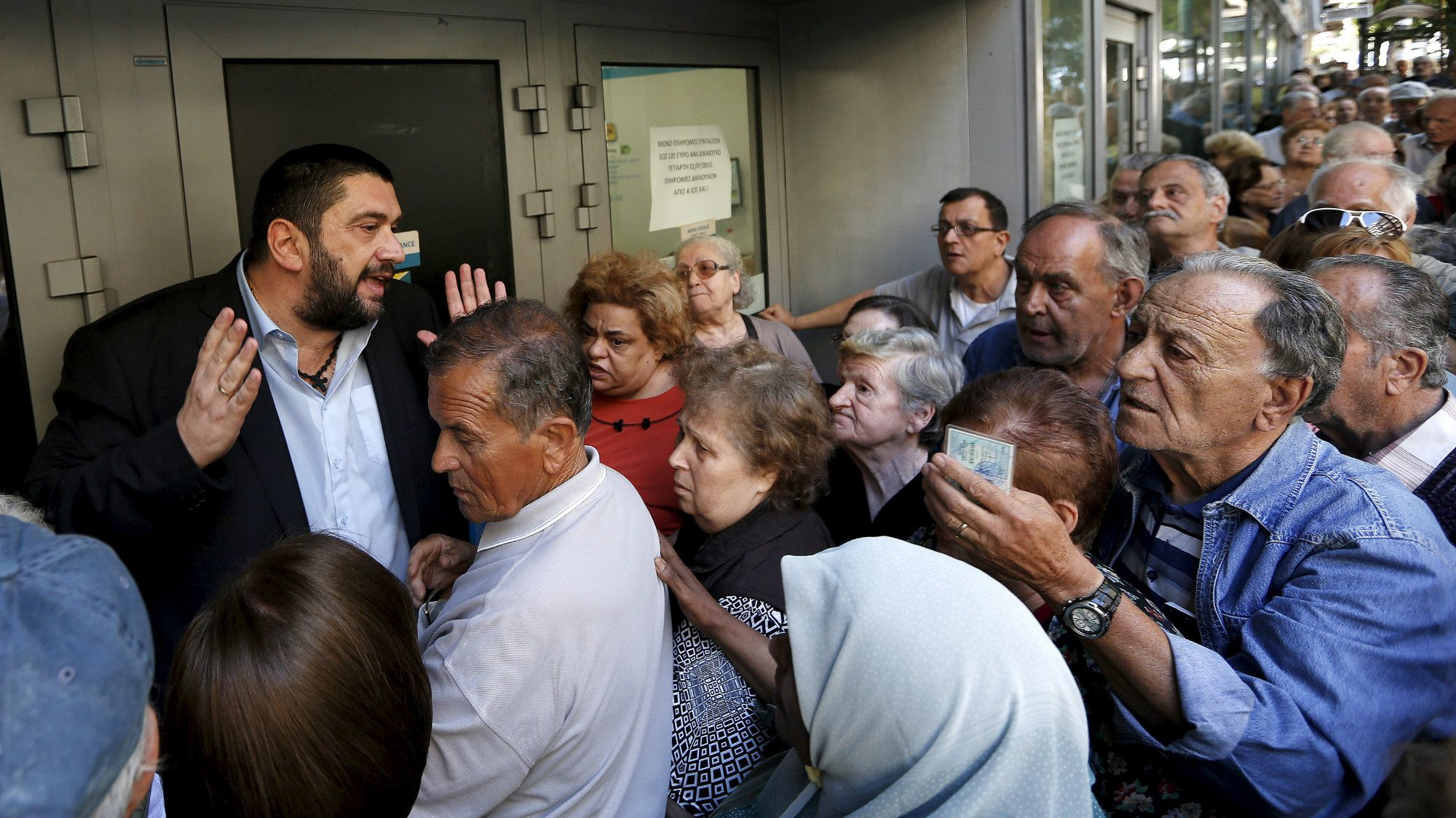 A bank manager tries to explain the situation to hundreds of pensioners queuing outside a National Bank branch in Athens, Greece, July 1, 2015.