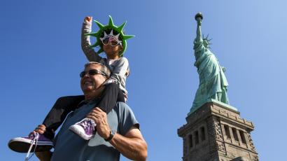 A girl mimics the Statue of Liberty as she poses for photos in front of the landmark ahead of the Independence Day holiday in New York July 3, 2015.