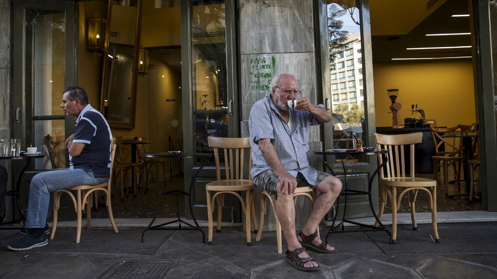 """People sit outside of a coffee shop in Athens, Greece, July 4, 2015. If a 'No' in Sunday's referendum eventually takes Greece out of Europe's single currency, any """"new drachma"""" or temporary payment unit could be worth as little as a fifth of the euro now in circulation. REUTERS/Marko Djurica"""