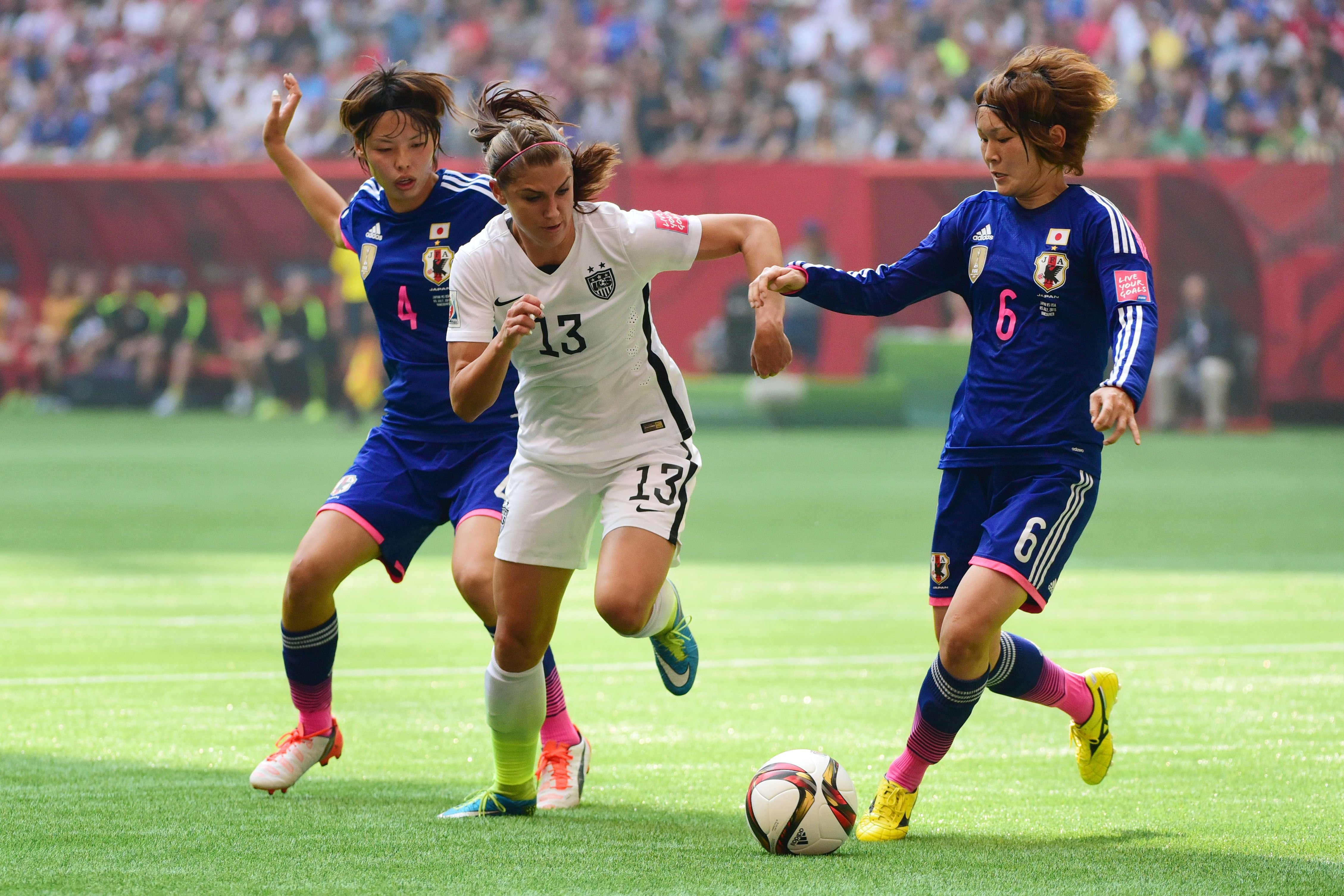 Jul 5, 2015; Vancouver, British Columbia, CAN; United States forward Alex Morgan (13) drives the ball between Japan defender Saki Kumagai (4) and midfielder Mizuho Sakaguchi (6) in the first half of the final of the FIFA 2015 Women's World Cup at BC Place Stadium.