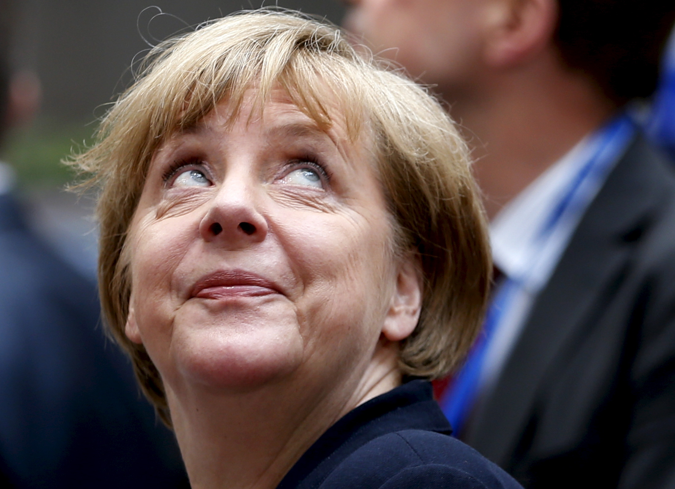 Germany's Chancellor Angela Merkel looks up as she arrives at an emergency euro zone summit in Brussels, Belgium, July 7, 2015. Greek Prime Minister Alexis Tsipras had a final chance to present credible reform proposals to an emergency euro zone summit on Tuesday to persuade skeptical creditors to reopen aid talks before his country's banks run out of money.
