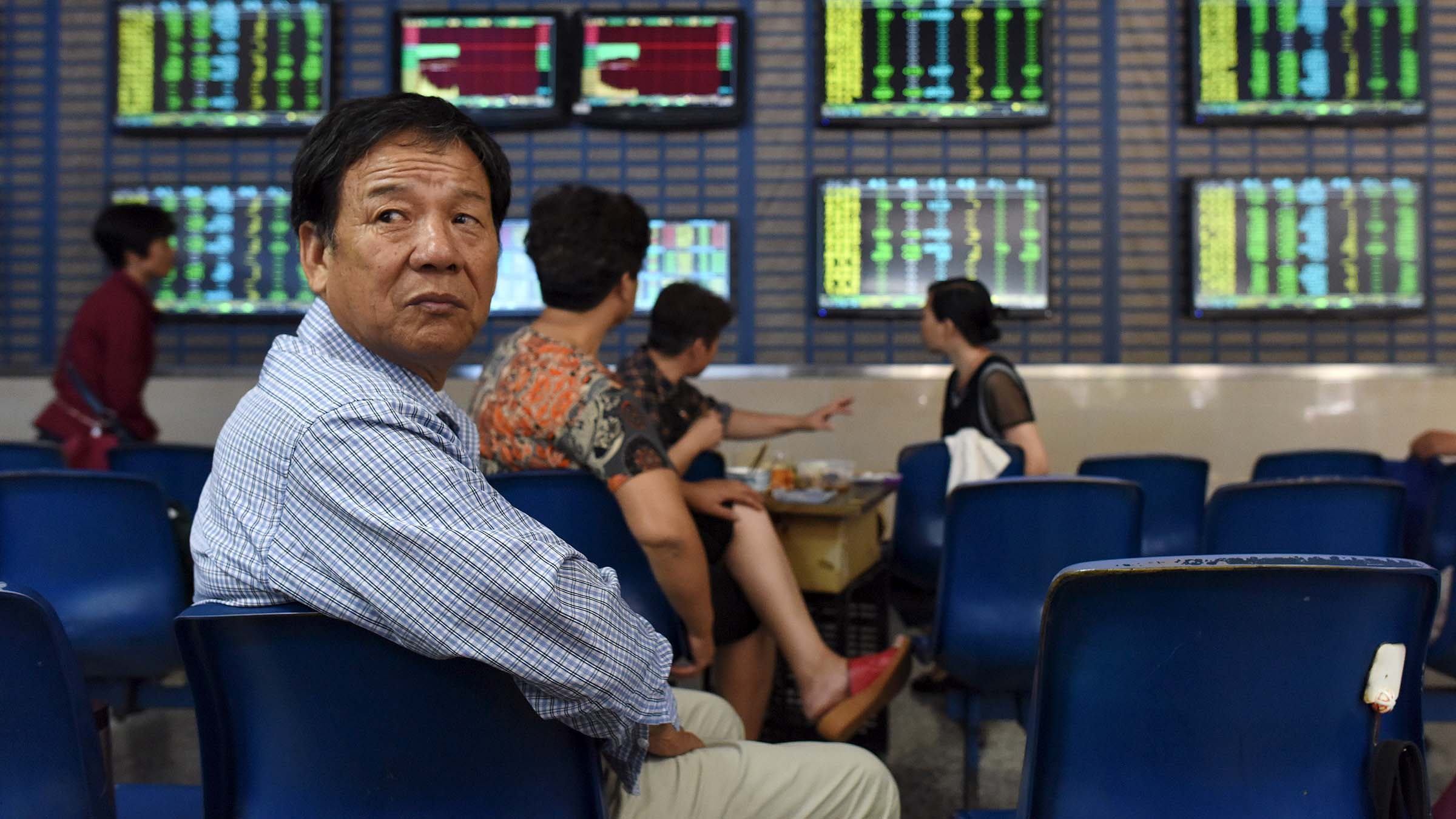 An investor looks over his shoulders as he sits in front of screens showing stock information, at a brokerage house in Hefei