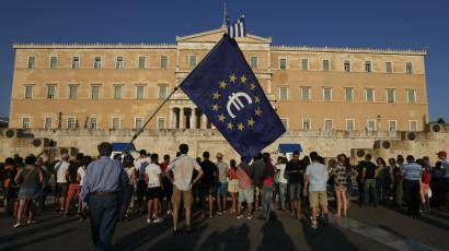 A protester holds a European Union flag with the Euro logo during a Pro-Euro rally in front of the parliament building in Athens, Greece.