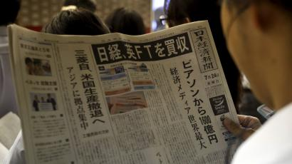A man reads the front page of Japan's Nikkei newspaper reporting Japanese media group Nikkei's acquisition of the Financial Times from Britain's Pearson at a train station in Tokyo
