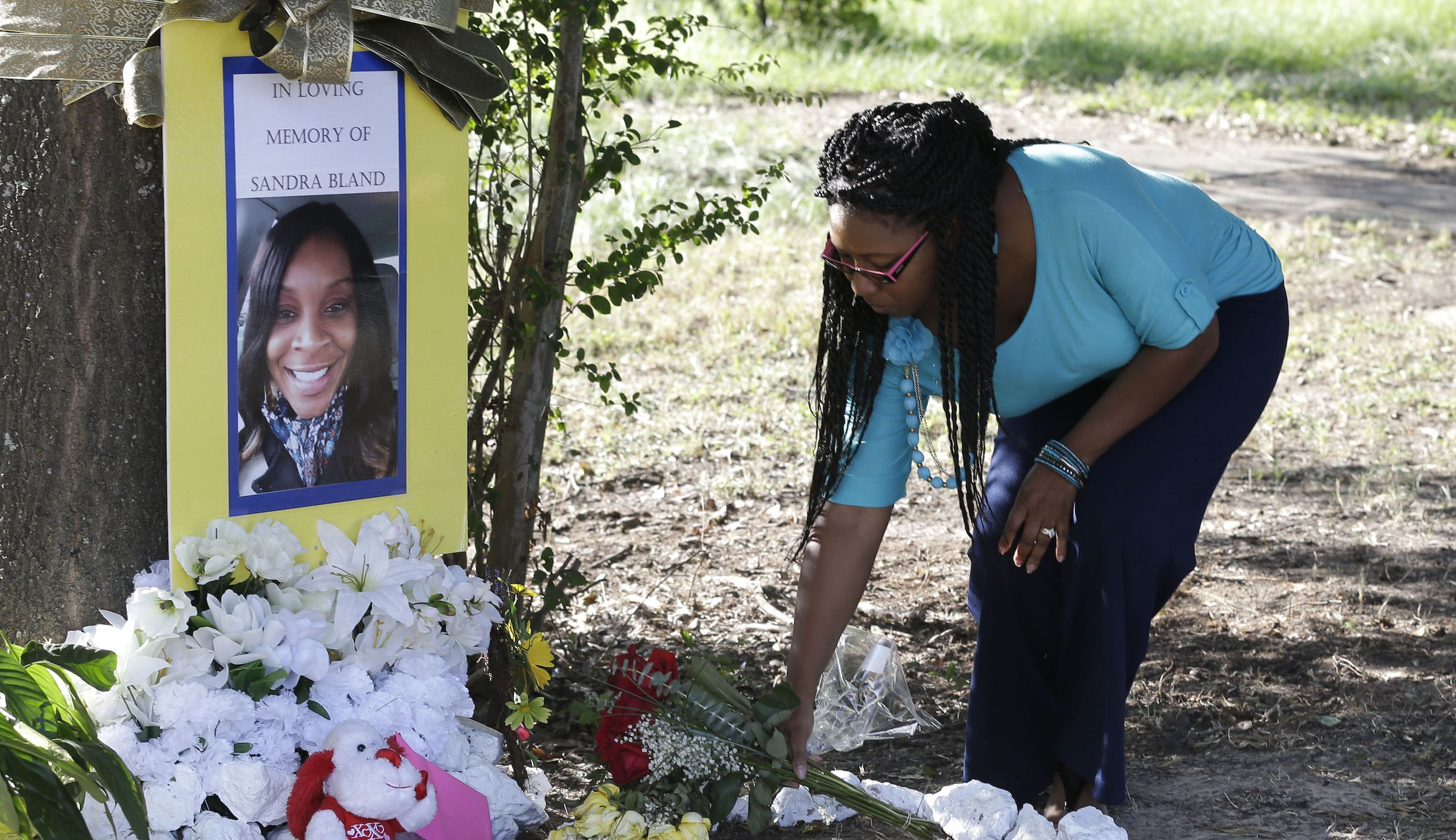 Jeanette Williams places a bouquet of roses at a memorial for Sandra Bland near Prairie View A&M University, Tuesday, July 21, 2015, in Prairie View, Texas. A newly released dashcam video documents how a routine traffic stop escalated into a shouting confrontation between a Texas state trooper and Bland, which led to her arrest. Bland was found hanging in her jail cell three days after the incident.