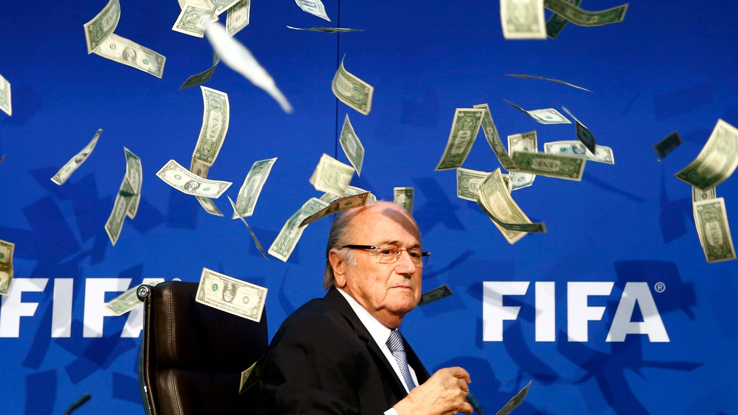 British comedian known as Lee Nelson (unseen) throws banknotes at FIFA President Sepp Blatter as he arrives for a news conference after the Extraordinary FIFA Executive Committee Meeting at the FIFA headquarters in Zurich, Switzerland July 20, 2015. World football's troubled governing body FIFA will vote for a new president, to replace Sepp Blatter, at a special congress to be held on February 26 in Zurich, the organisation said on Monday.