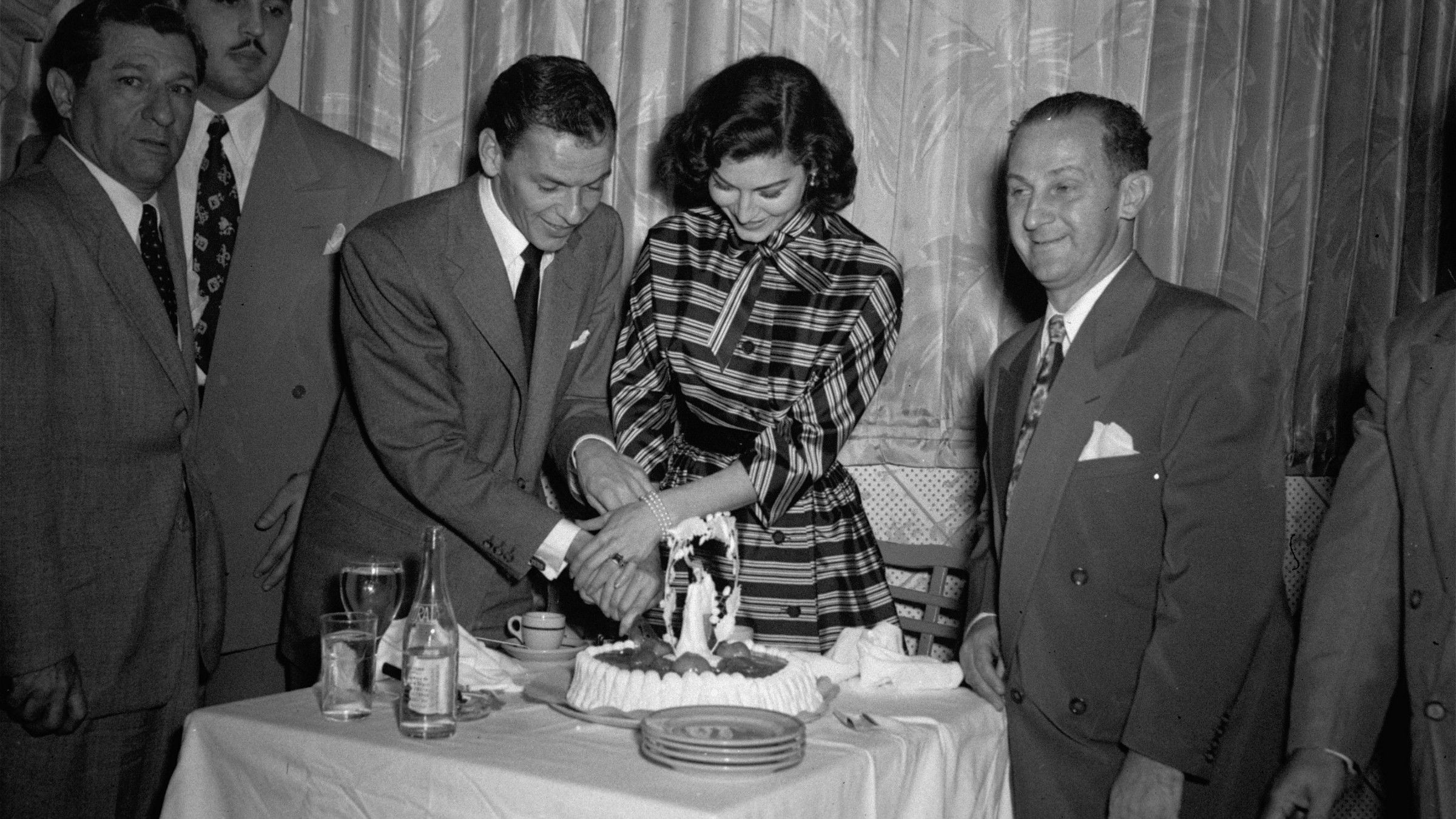 Frank Sinatra and his new bride, movie actress Ava Gardner, join hands as they cut a wedding cake in the Montmarte, a Havana, Cuba, nightclub November 8, 1951. Married November 7, in Philadelphia, they went to Havana on a whirlwind honeymoon.