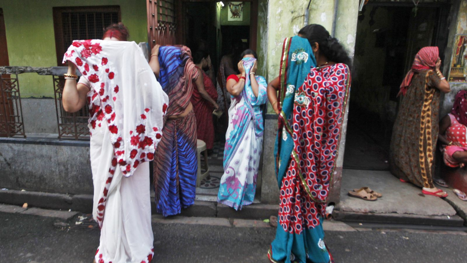 Indian sex workers cover their faces as they react to the camera while watching a rally as part of the week-long sex workers' freedom festival at the Sonagachi red-light area in Kolkata July 24, 2012. In the global battle against HIV/AIDS, sex workers like those in Sonagachi, one of Asia's largest red light districts, are a crucial link in a chain of infection that some 20,000 experts gathered in Washington are debating how to break -- but without having foreign sex workers there. Picture taken on July 24, 2012. To match story INDIA-SEXWORKERS/