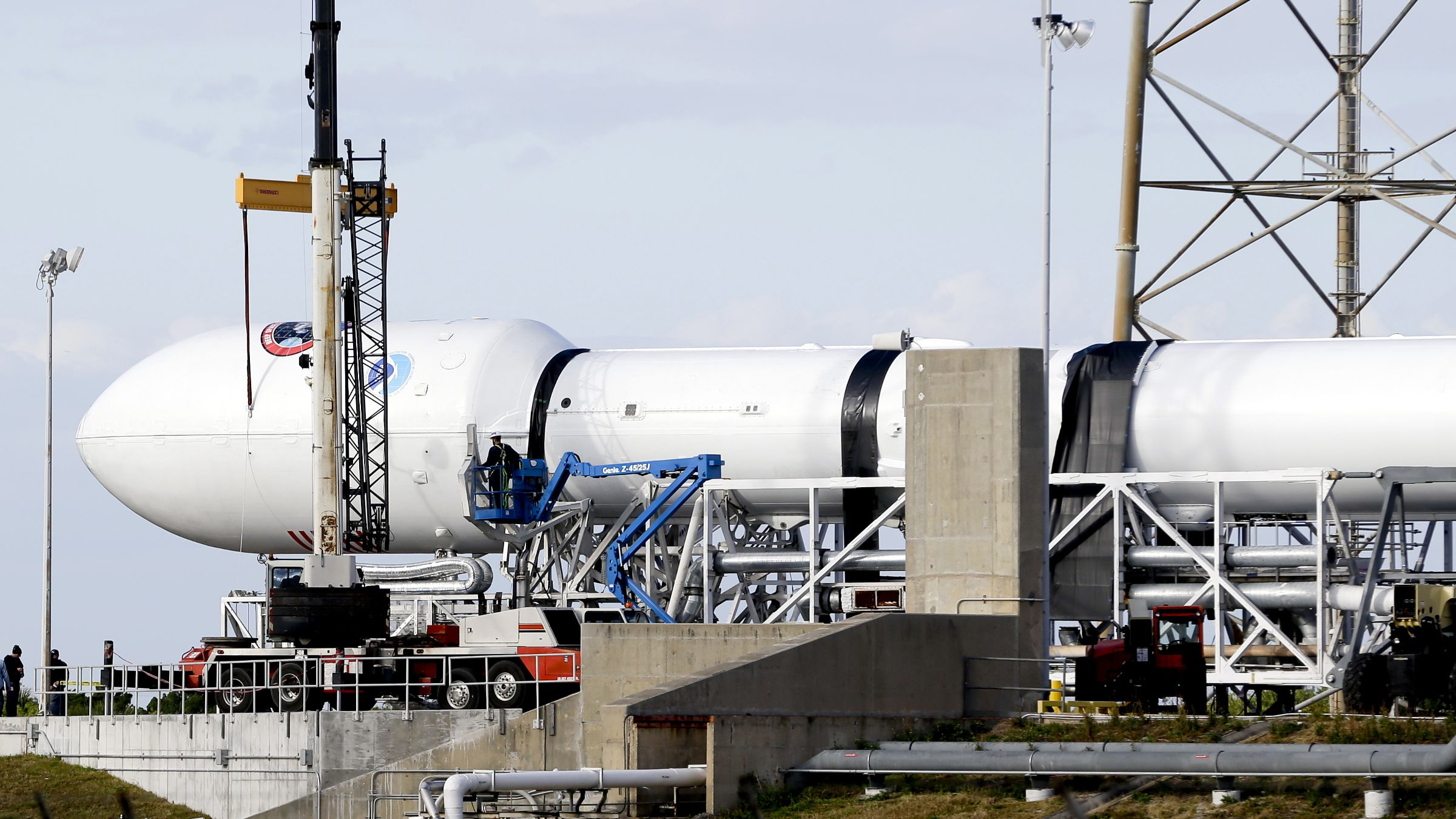 Maintenance is performed by workers on the Falcon 9 SpaceX rocket at launch complex 40 at the Cape Canaveral Air Force Station in Cape Canaveral, Fla., Monday, Feb. 9, 2015. The Sunday launch attempt was scrubbed and SpaceX will try again on Tuesday evening, Feb. 10.