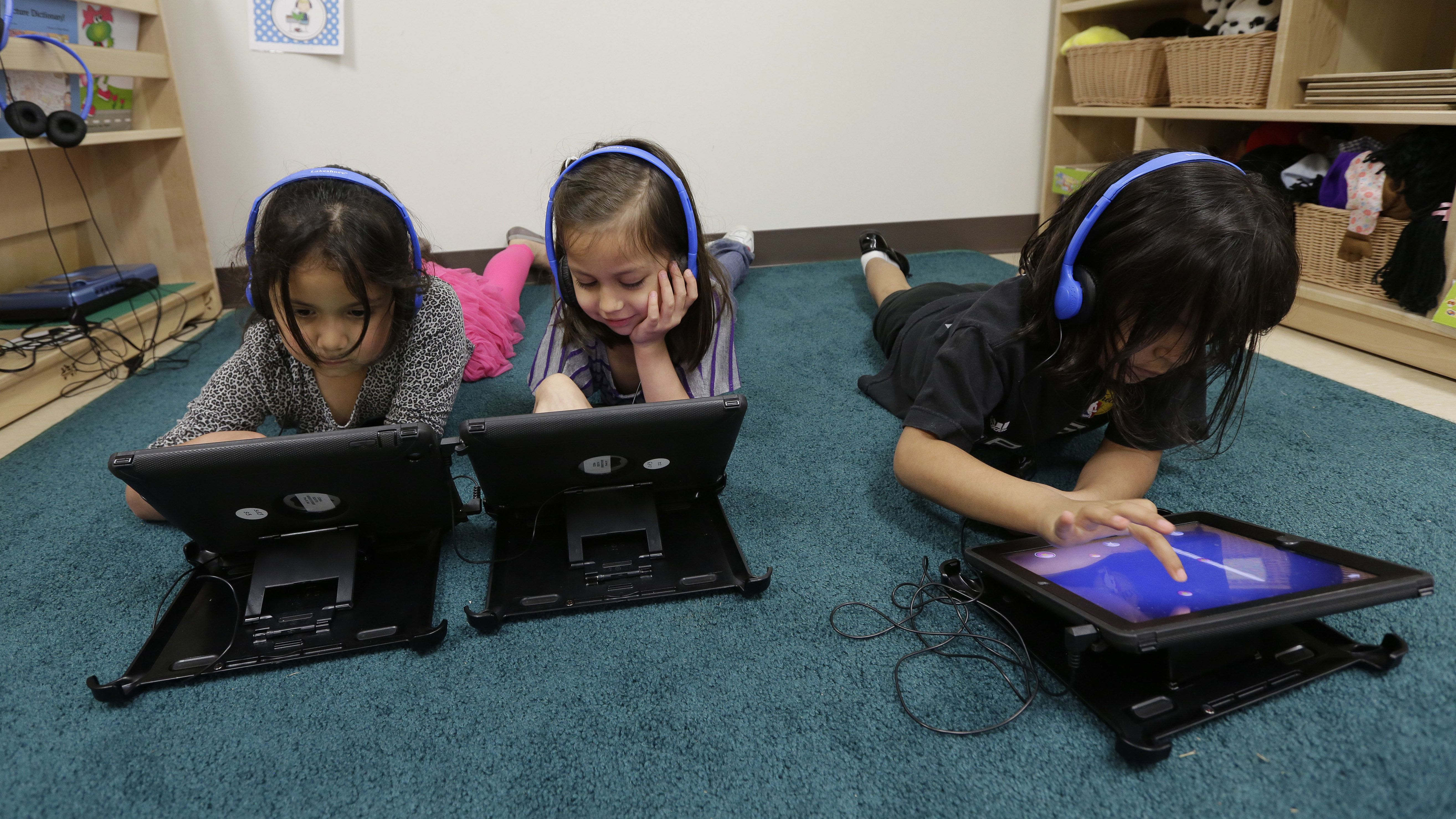 FILE - In this April 2, 2014 file photo, Pre-K students use electronic tablets at the South Education Center, in San Antonio. As Gov. Rick Perry wraps up a record 14 years on the job, Republican Greg Abbott and Democrat Wendy Davis are both vowing to make public schools a top-line agenda if elected in November. Following through could make public schools a signature issue for a Texas governor as it was under George W. Bush, before he left for the White House and used the state's testing system as the framework for No Child Left Behind. (AP Photo/Eric Gay, File)