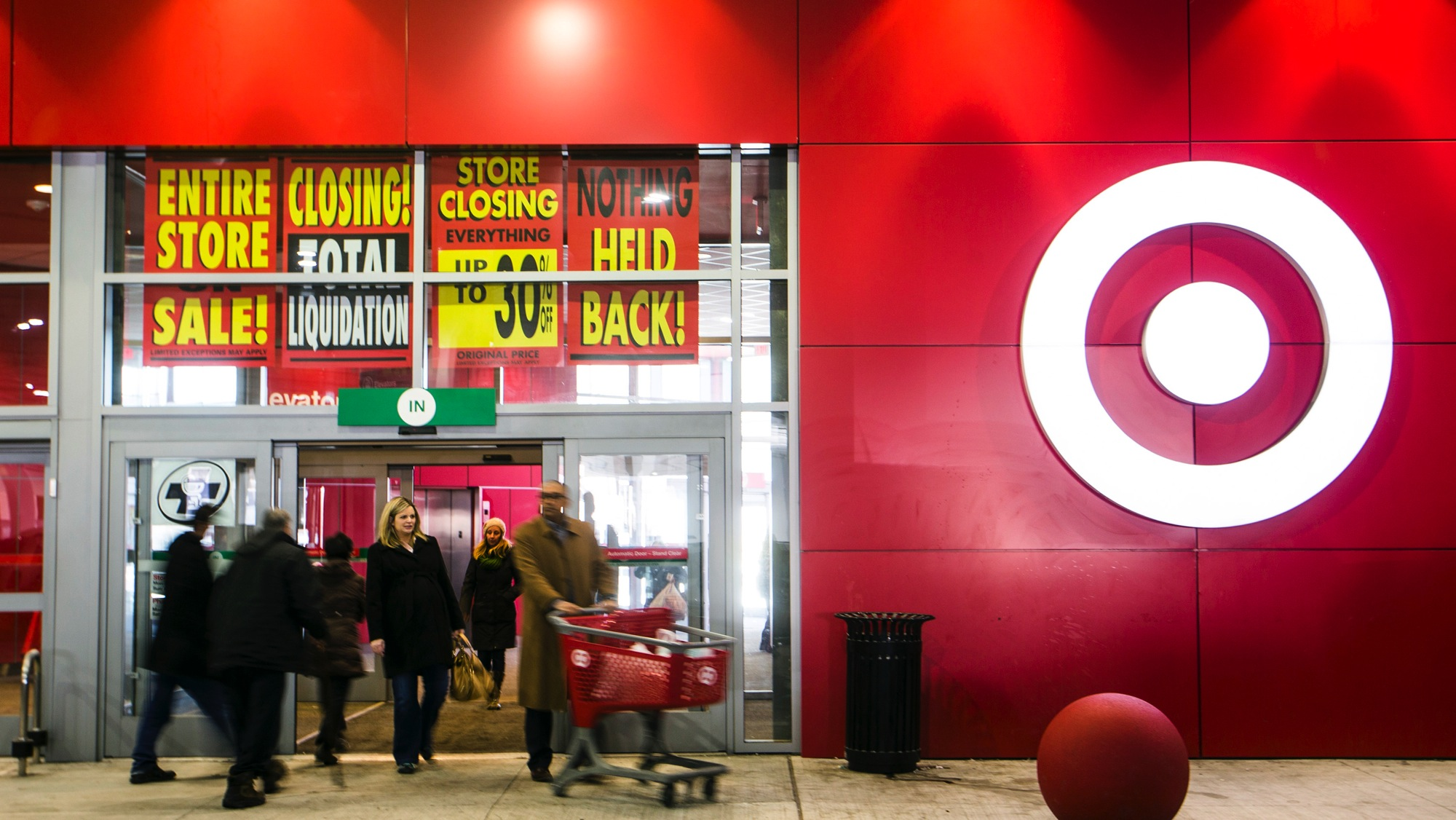 People walk out of the going-out-of-business sale at Target Canada in Toronto February 5, 2015. Target Corp is closing its stores in Canada after the insolvent retailer came to an agreement with its landlords to start liquidation. REUTERS/Mark Blinch (CANADA - Tags: BUSINESS)