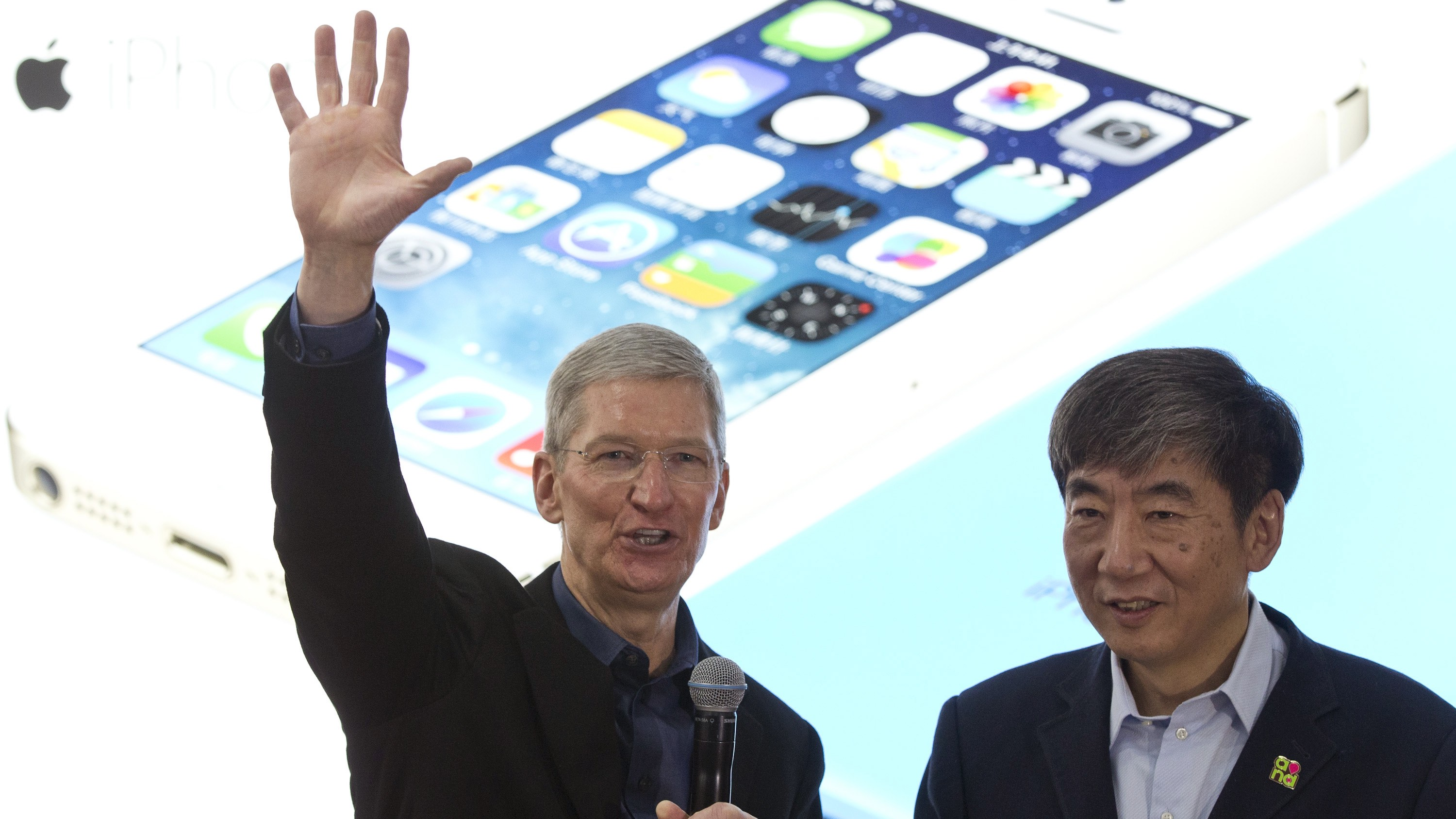 Apple's CEO Tim Cook, left, gestures as China Mobile's chairman Xi Guohua looks on during a promotional event that marks the opening day of sales of China Mobile's 4G iPhone 5s and iPhone 5c at a shop of the world's largest mobile phone operator in Beijing, China, Friday, Jan. 17, 2014. (AP Photo/Alexander F. Yuan)