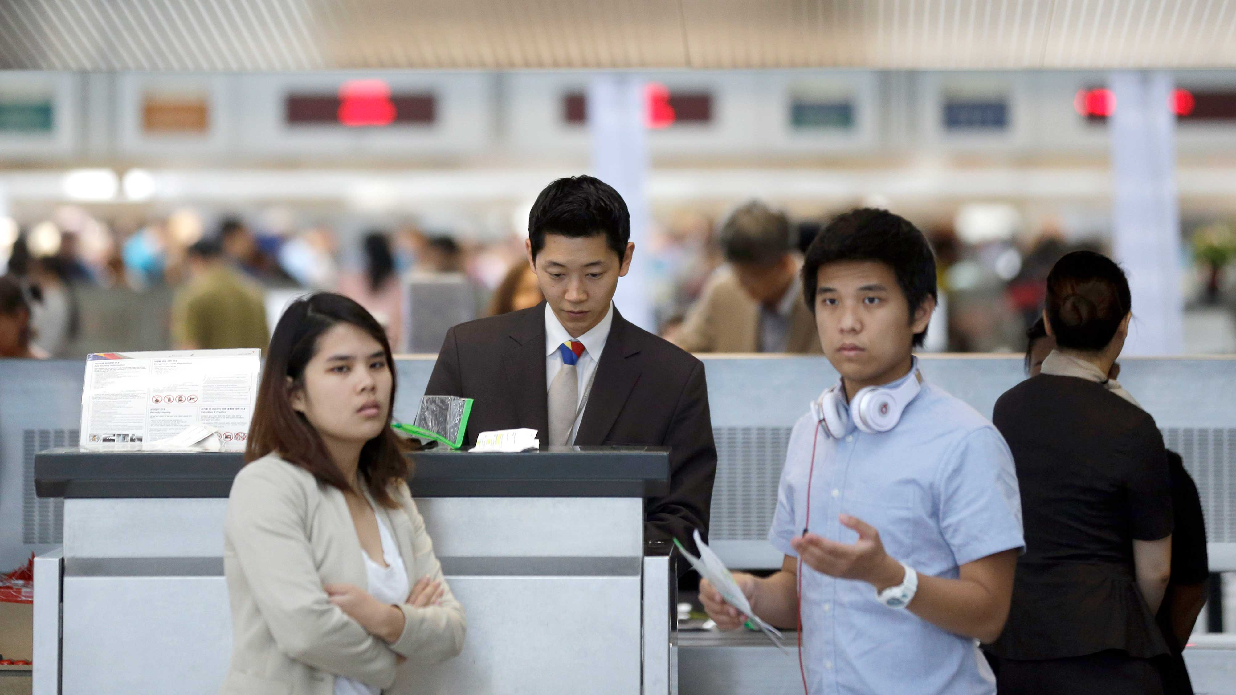 Passengers check in at the Asiana Airlines ticket counter at the San Francisco International Airport in San Francisco, Sunday, July 7, 2013