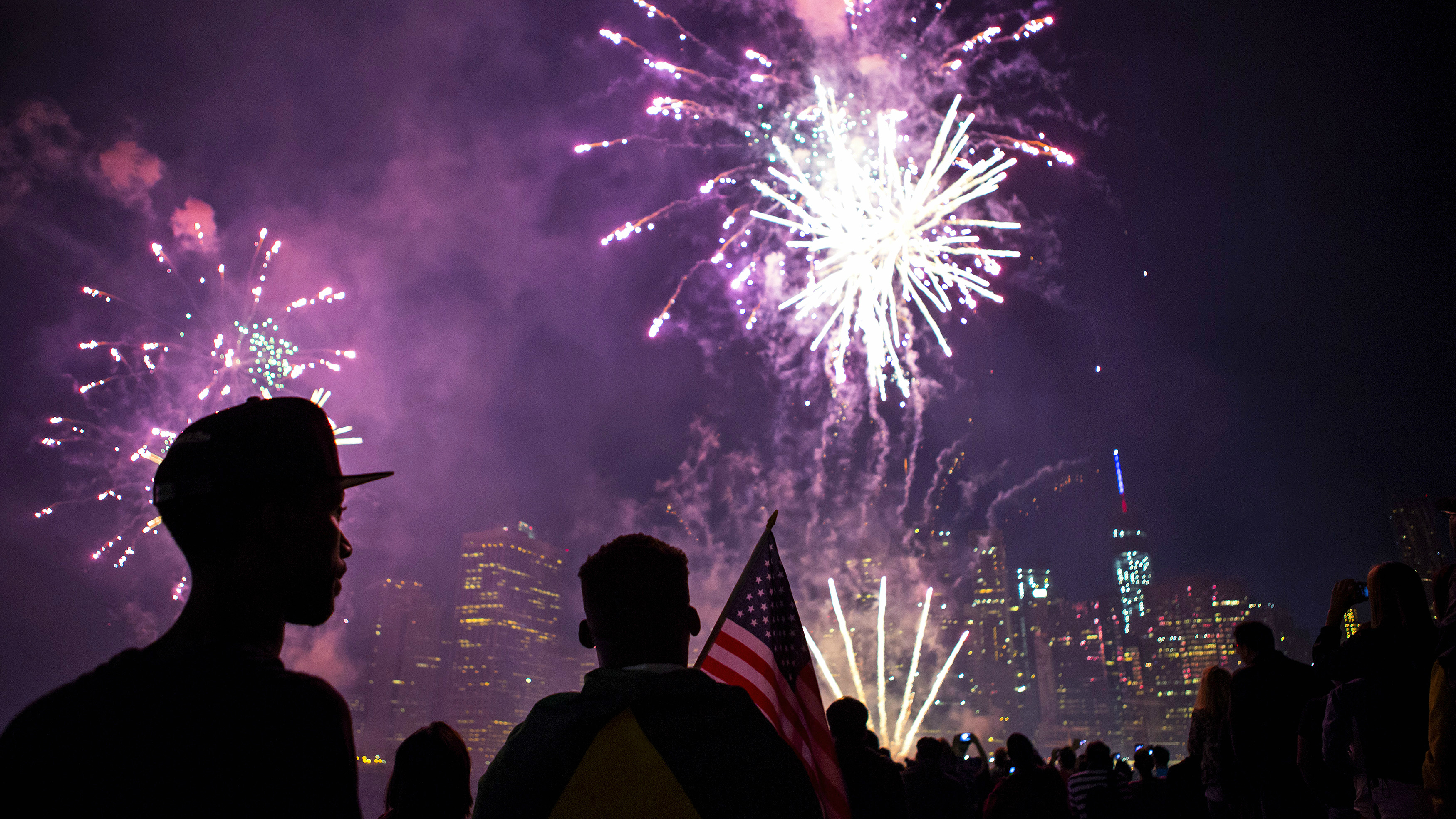 The skyline of lower Manhattan is seen as spectators watch Macy's Fourth of July fireworks explode over the East River in New York July 4, 2014. Hotdog eating champs, backyard picnickers and small-town parade lovers pressed on with July Fourth celebrations, some with less sizzle after wet weather on the U.S. East Coast postponed fireworks shows. REUTERS/Eric Thayer (UNITED STATES - Tags: CITYSCAPE ANNIVERSARY SOCIETY)