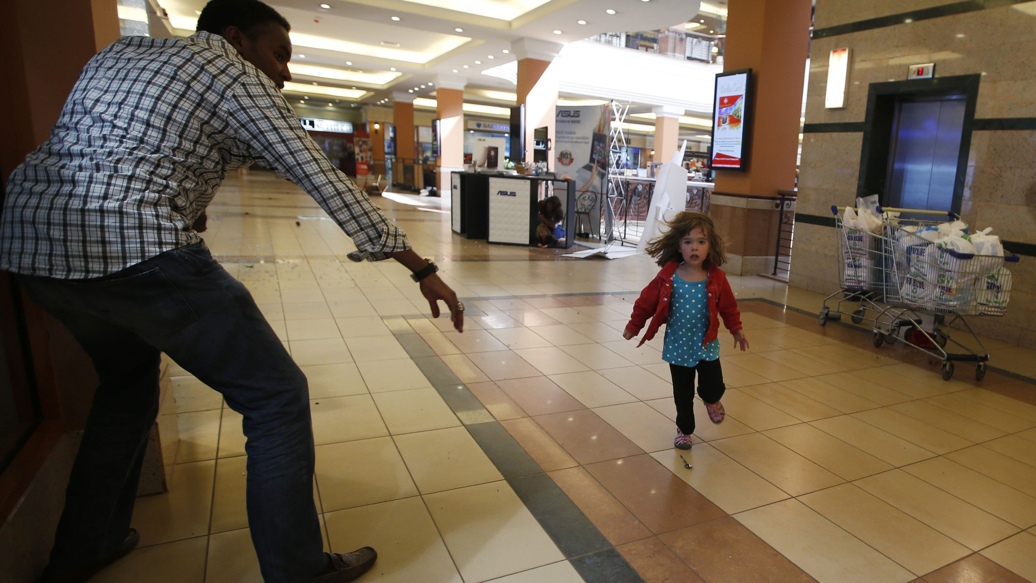 A child runs to safety as armed police hunt gunmen who went on a shooting spree at Westgate shopping centre in Nairobi September 21, 2013. The gunmen stormed a shopping mall in Nairobi on Saturday killing at least 20 people in what Kenya's government said could be a terrorist attack, and sending scores fleeing into shops, a cinema and onto the streets in search of safety.