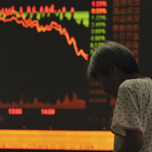 An investor stands in front of an electronic board showing stock information at a brokerage house in Fuyang, Anhui province, July 27, 2015. China stocks plunged more than 8 percent, their biggest one-day drop in more than eight years. REUTERS/Stringer