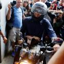 Outgoing Greek Finance Minister Yanis Varoufakis tries to leave on his motorcycle surrounded by media, after his resignation in Athens, Monday, July 6, 2015. Greece and its membership in Europe's joint currency faced an uncertain future Monday, with the country under pressure to reach a bailout deal with creditors as soon as possible after Greeks resoundingly rejected the notion of more austerity in exchange for aid.