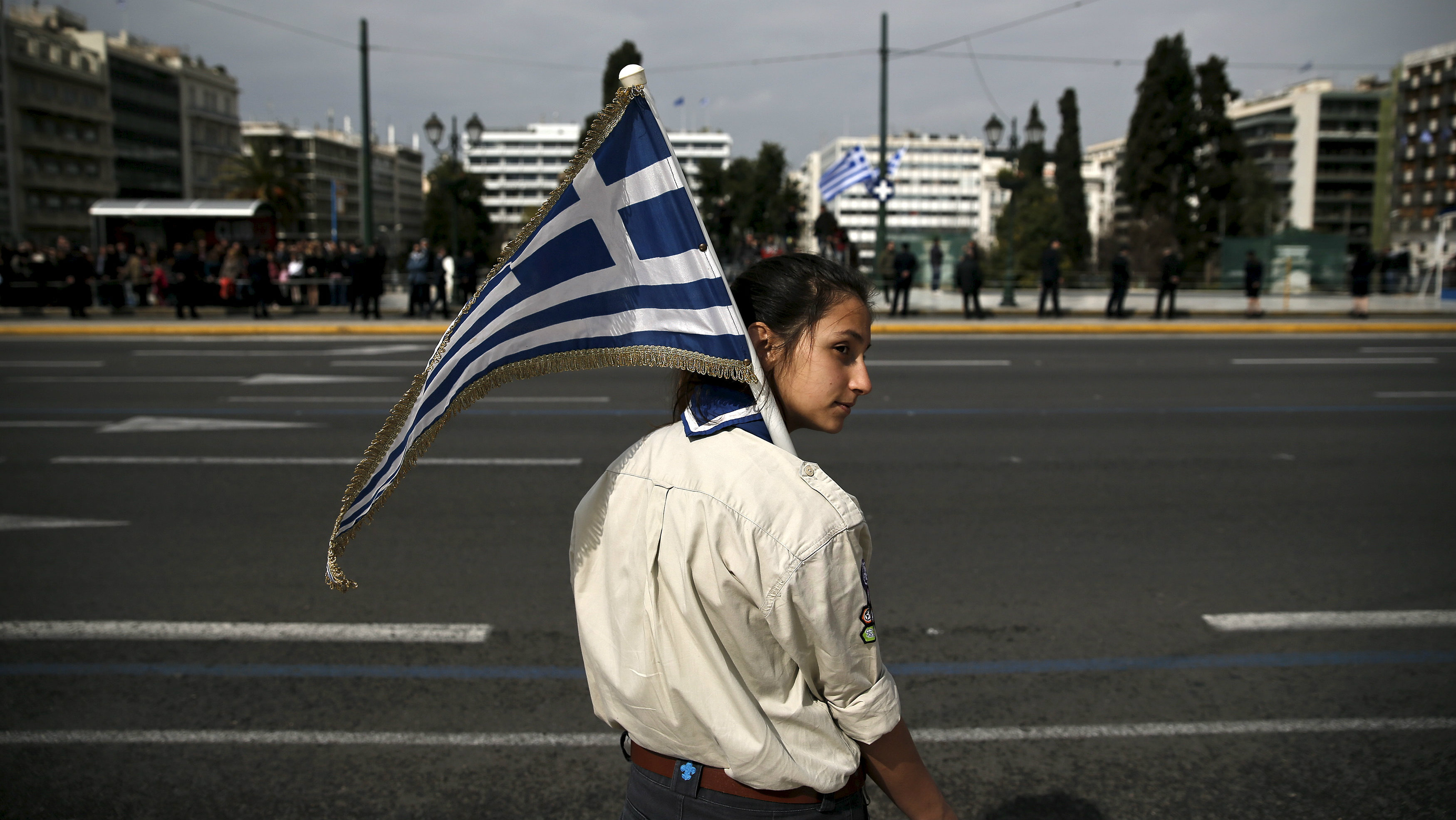 A girl scout holds a Greek national flag ahead of a student parade in Athens March 24, 2015, a day before a military parade to mark Greece's Independence Day. Greece said it will present a package of reforms to its euro zone partners by next Monday in hope of unlocking aid to help it deal with a cash crunch and avoid default.