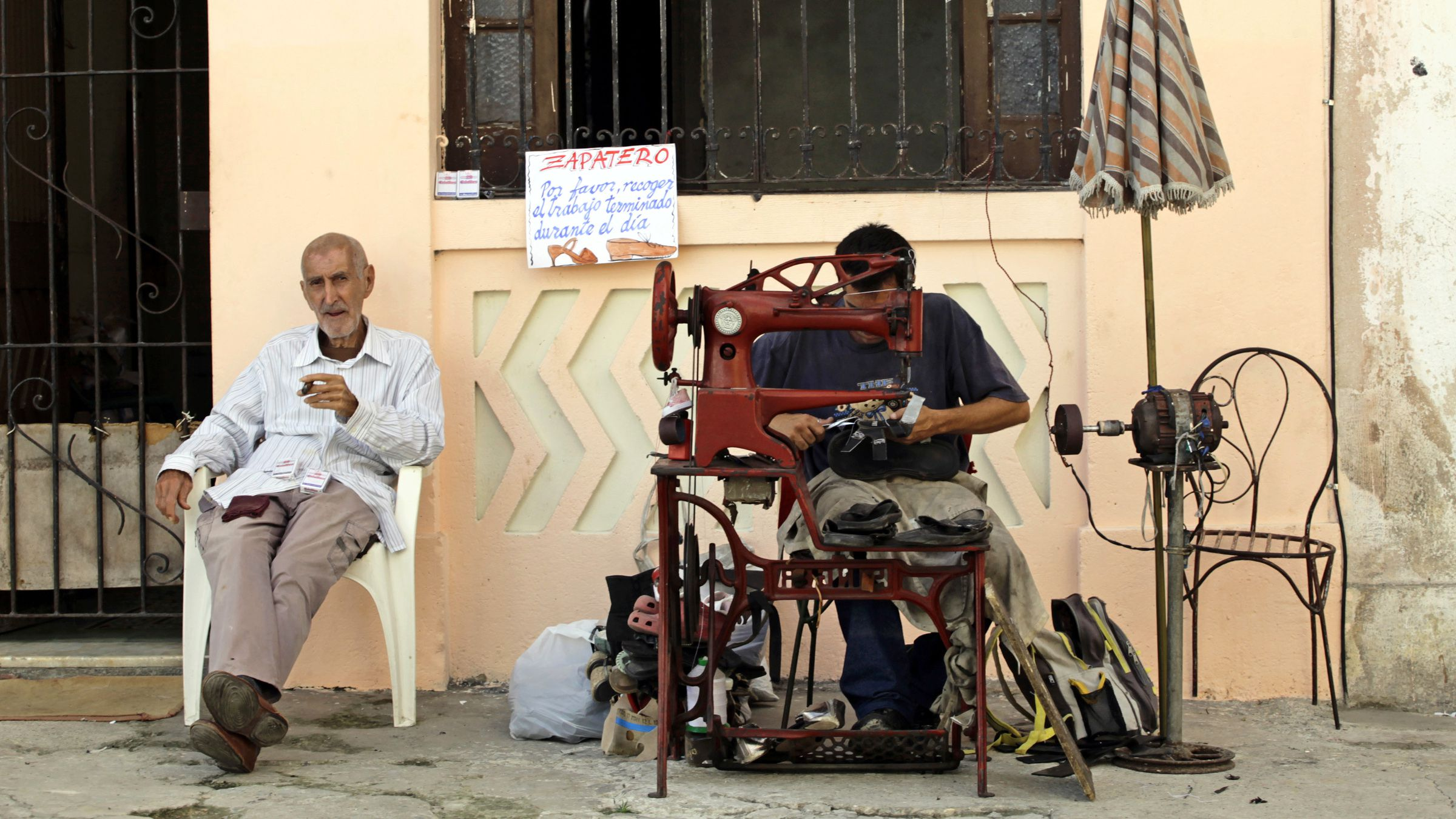 A privately licensed shoe repairman (R) works along a street in Havana February 2, 2012. Unseen in the past, private entrepreneurs are an example of how life is changing in Cuba since President Raul Castro launched a string of limited economic reforms, legalizing certain kinds of businesses, including restaurants, hostels and street vendors. Picture taken February 2, 2012. To match Special Report CUBA-ECONOMY/REFORMS